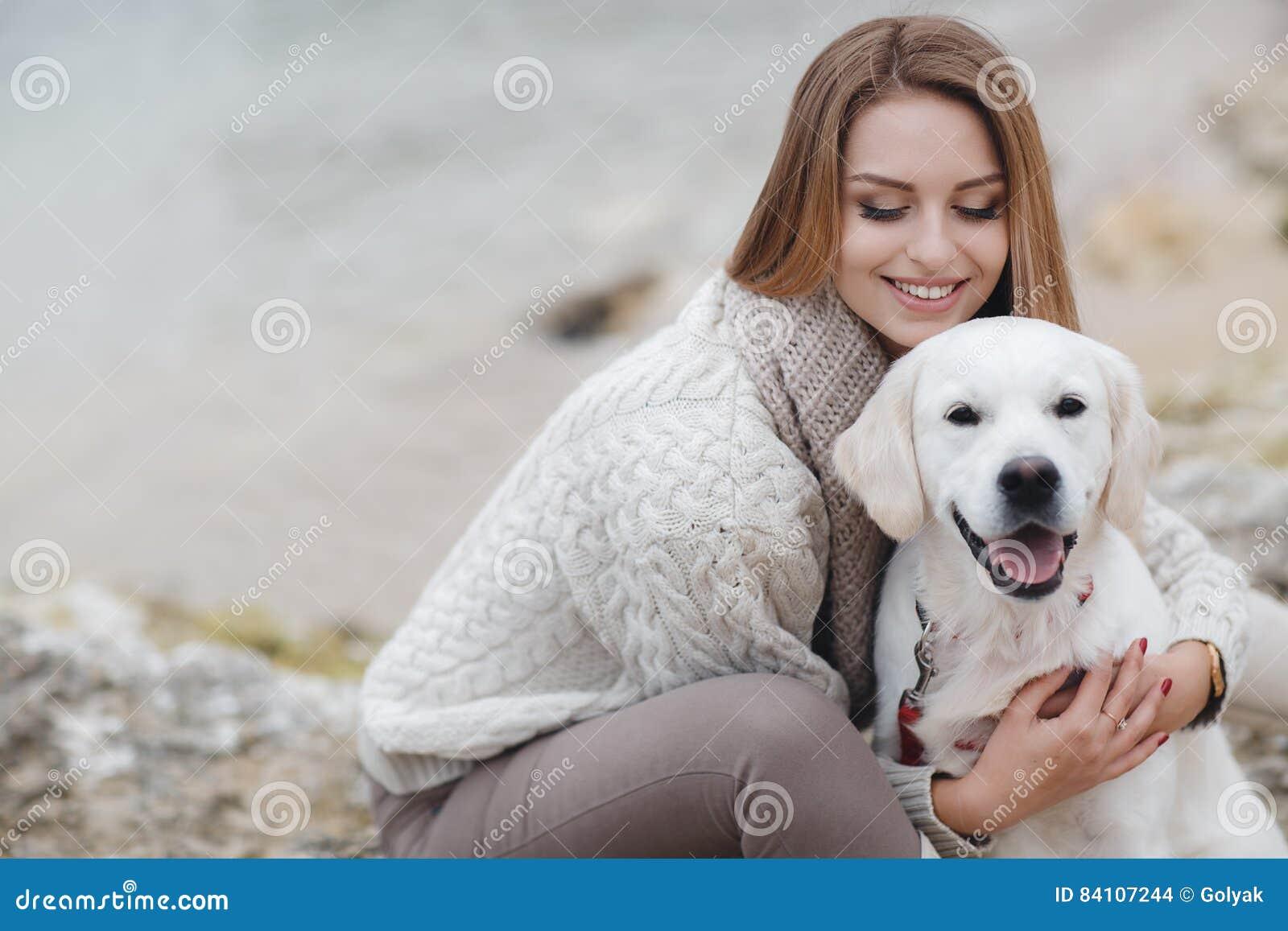 Frau mit Hund auf dem Seeufer