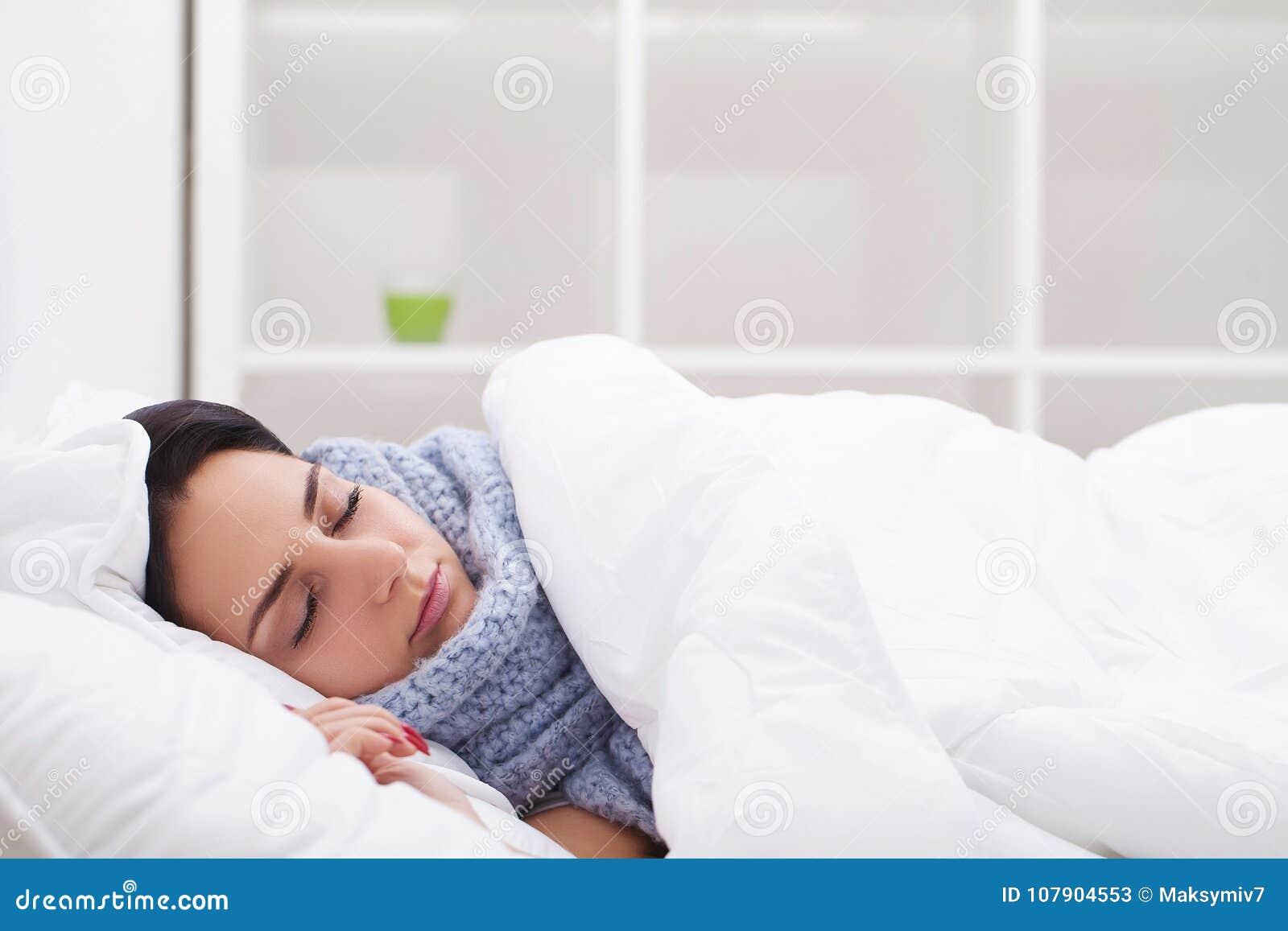 Frau mit kranken Kälten des Thermometers, Grippe, Fieber, Kopfschmerzen im Bett