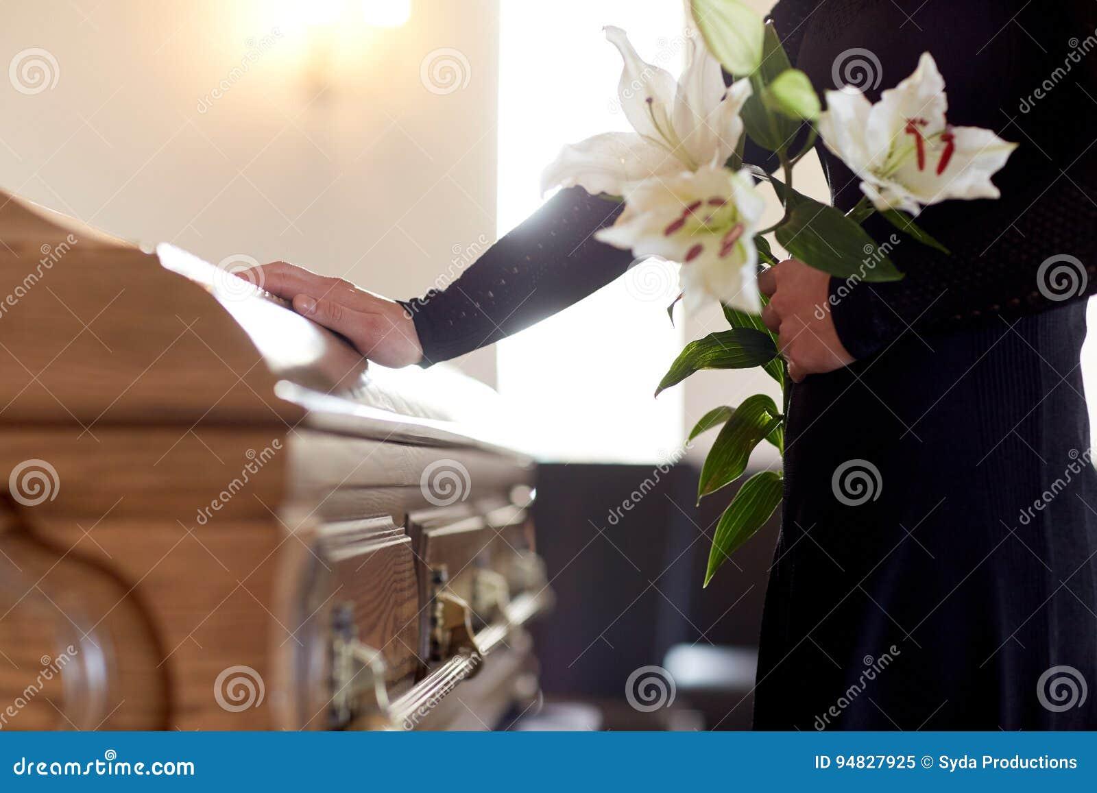 Frau mit Lilienblumen und -sarg am Begräbnis