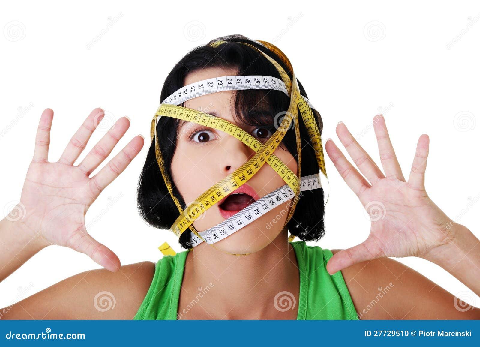 Frau mit messendem Band um ihren Kopf