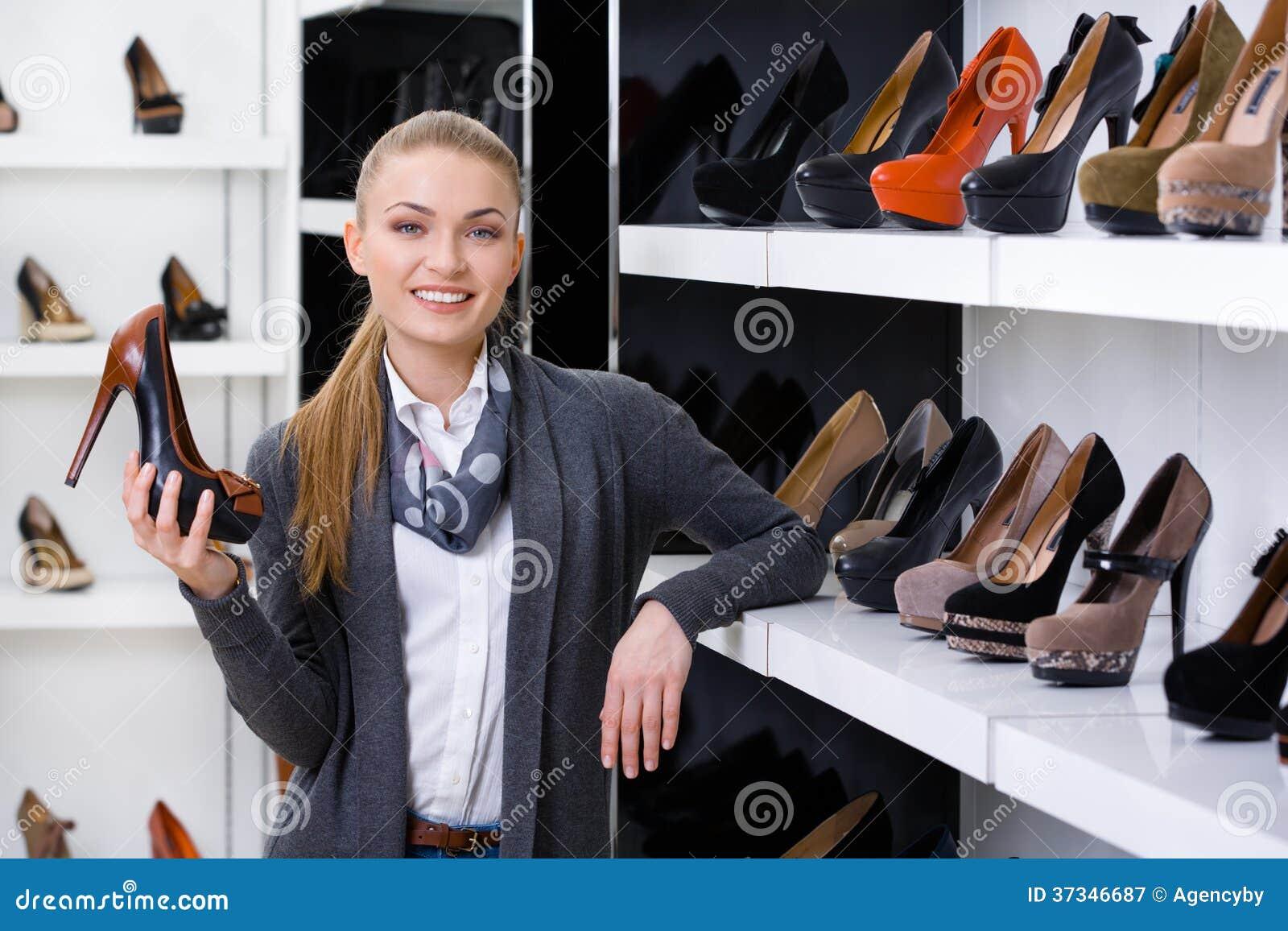 Frau mit Schuh wählt in der Hand Stöckelschuhe
