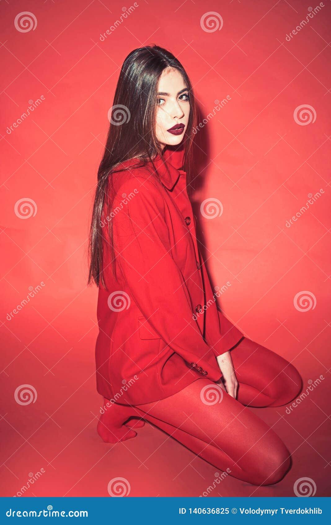 Frau mit stilvollem Make-up und langen dem Haar, die in der roten totalausstattung aufwirft Art und Weisekonzept Mädchen auf ruhi