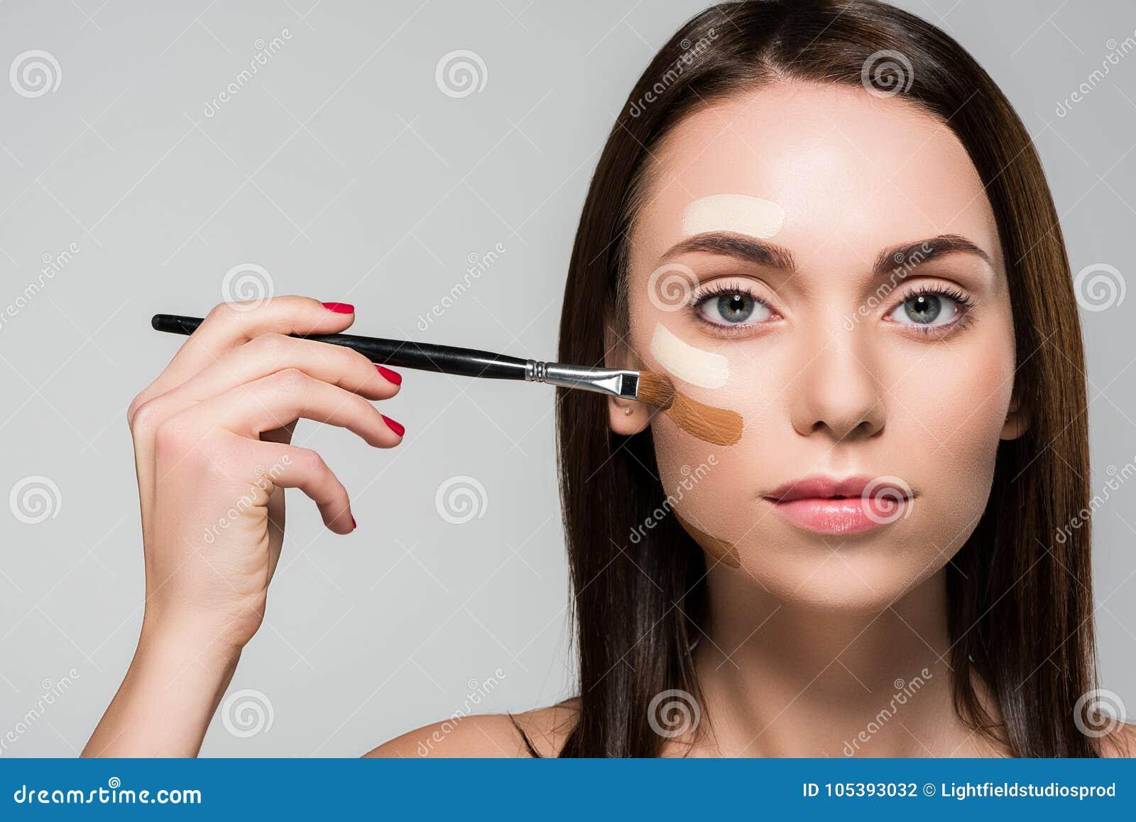 Frau mit Ton- Grundlage auf Gesicht