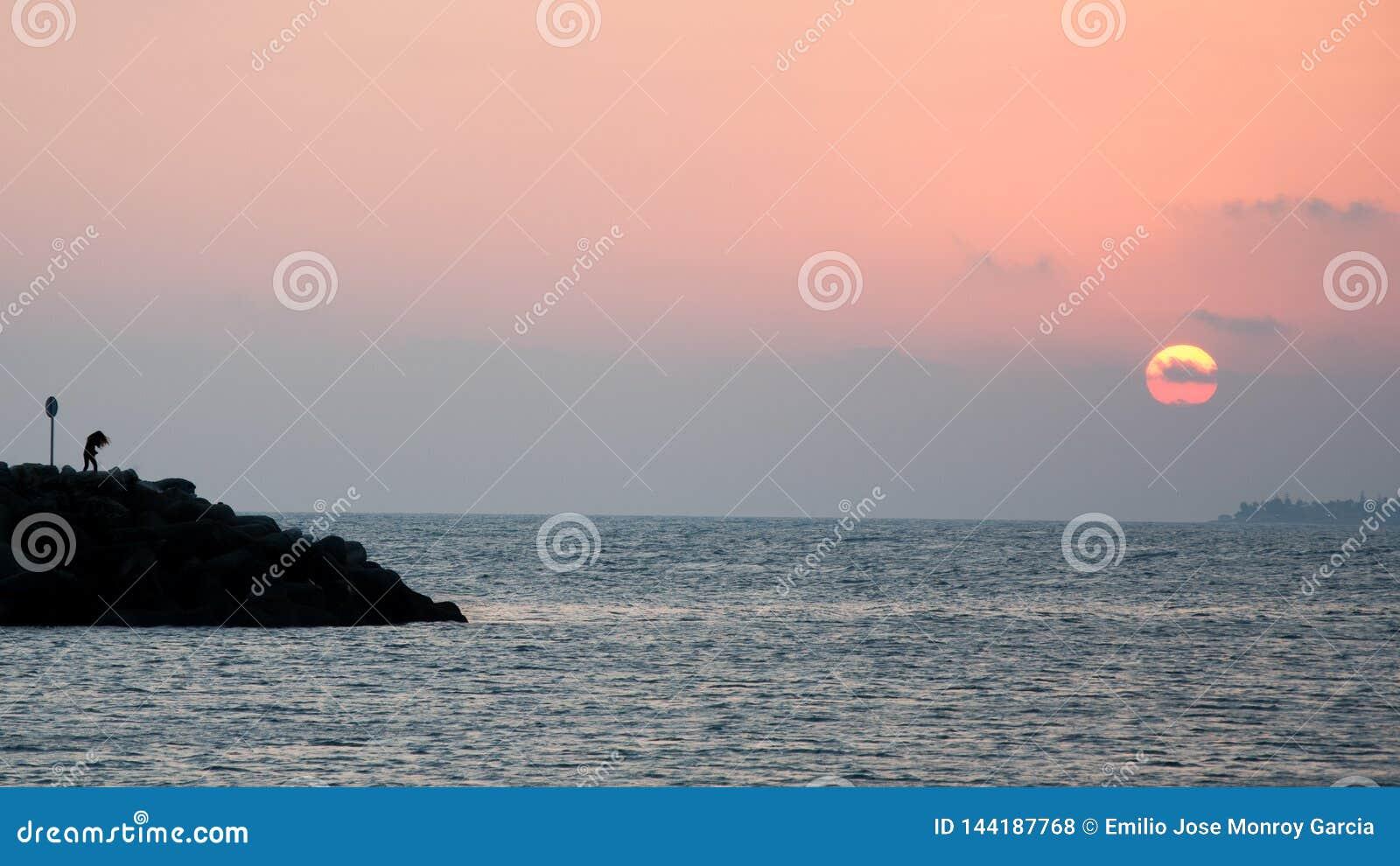 Frau nahe bei dem Meer bei Sonnenuntergang