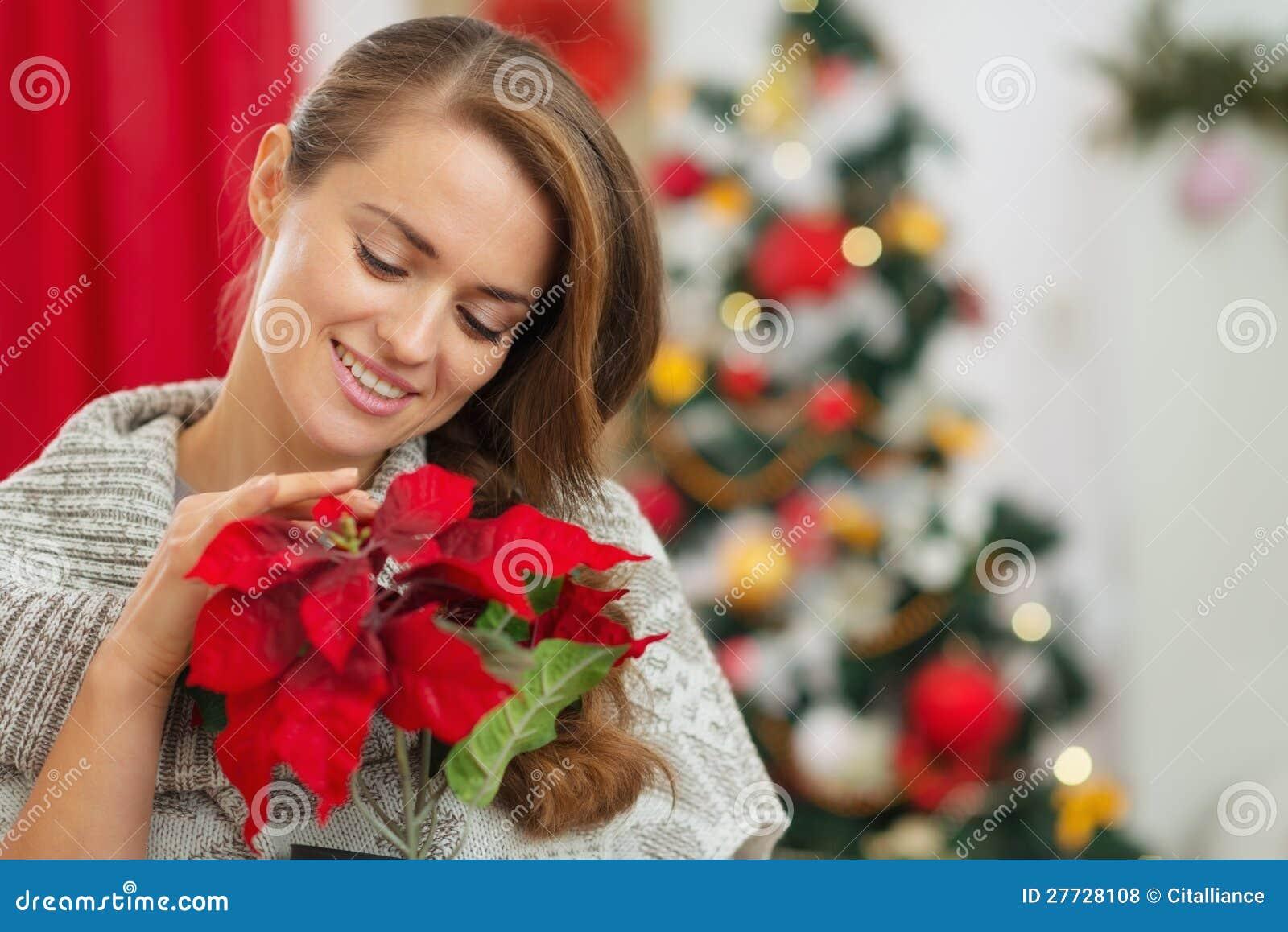 Frau nahe Weihnachtsbaum-Holding Weihnachten stieg