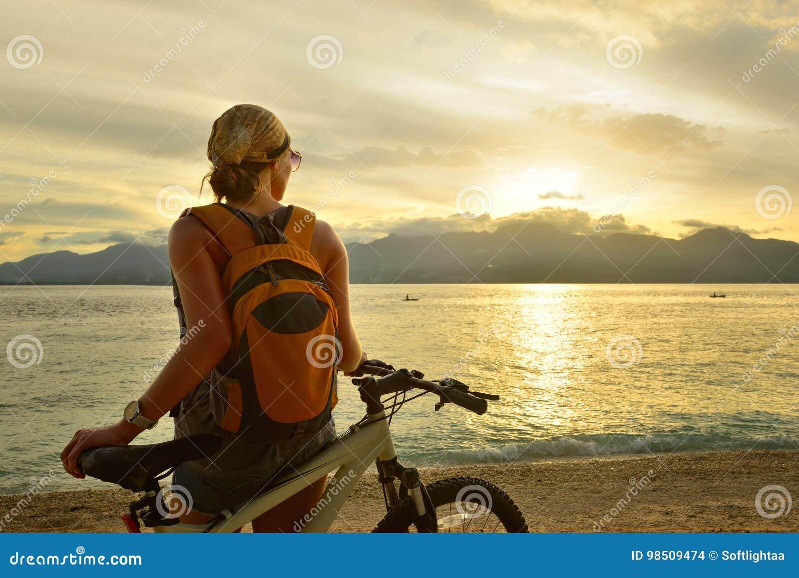 Frau reist mit einem Rucksack auf ihrem Fahrrad