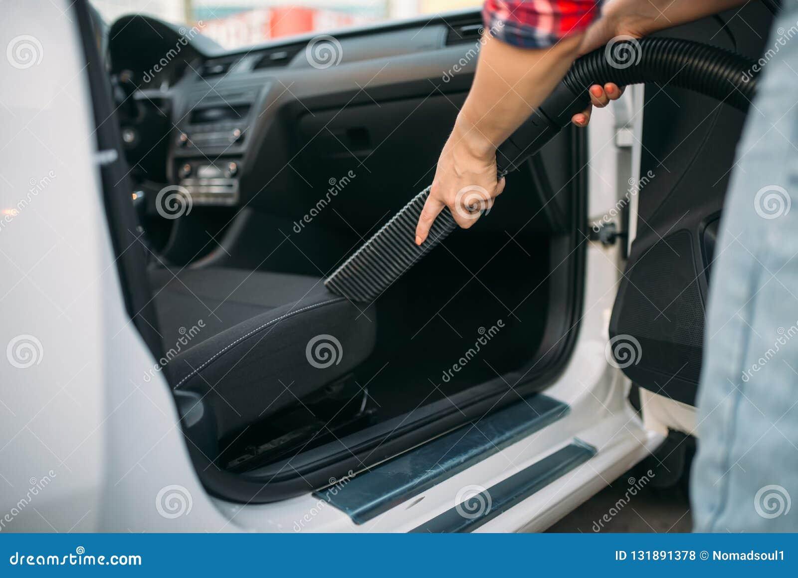 Frau säubert Autoinnenraum mit Staubsauger