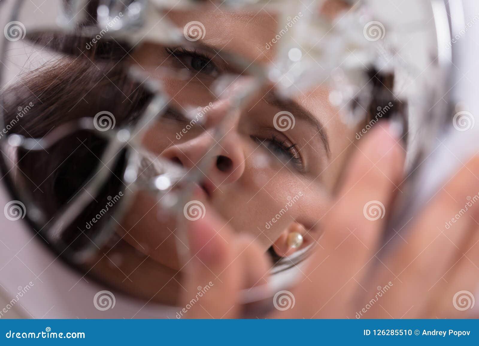 Frau ` s Gesicht in defektem Spiegel