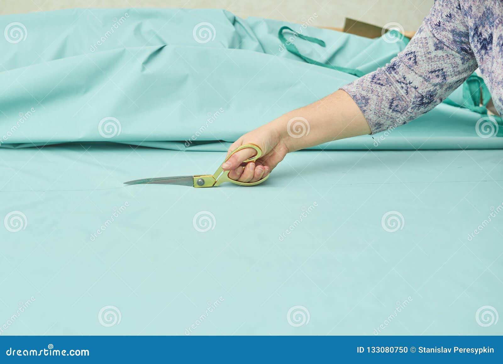 Frau schneidet blaues Material mit goldenen Scheren