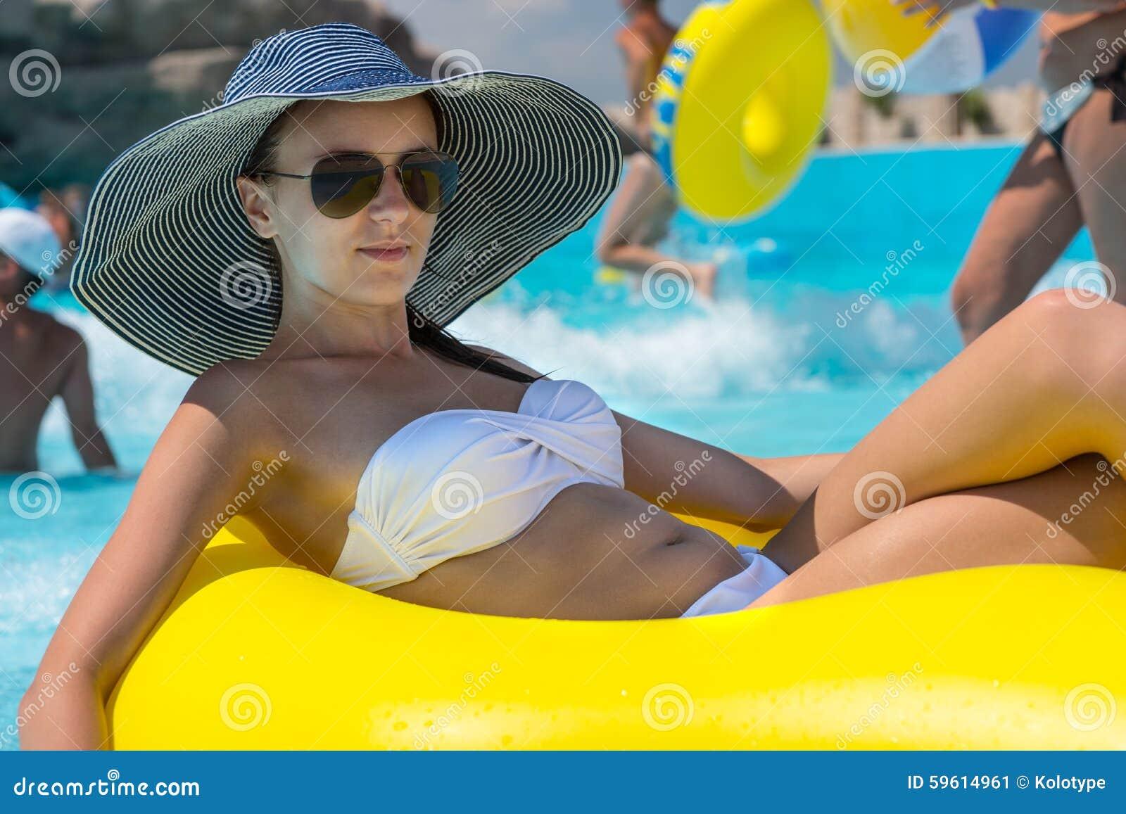Frau in Sun-Hut, der in Pool-inneres Rohr schwimmt