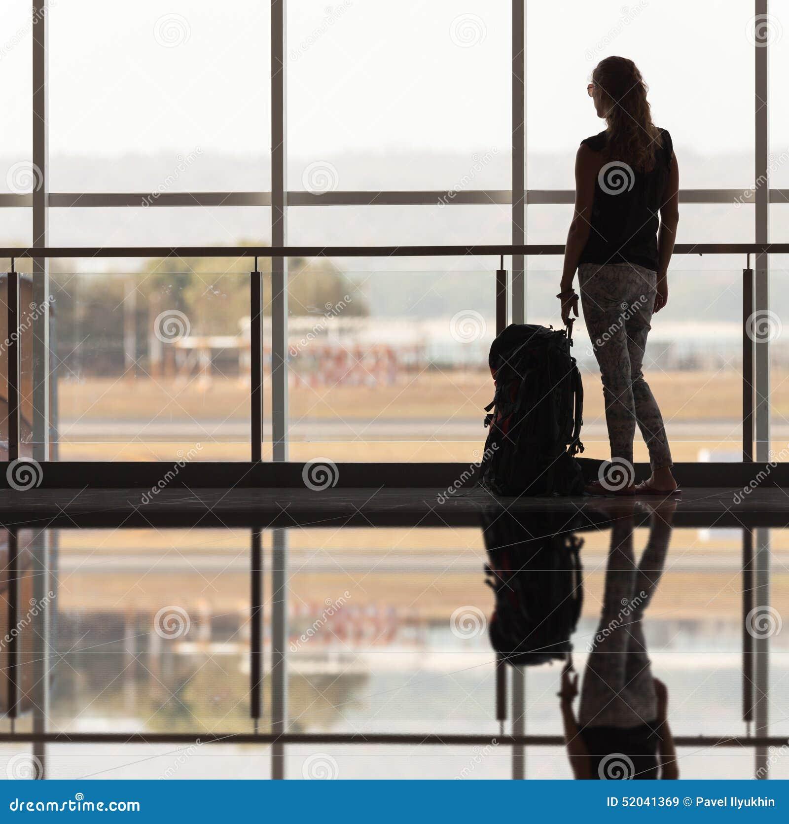 Frau trägt Ihr Gepäck am Flughafenabfertigungsgebäude