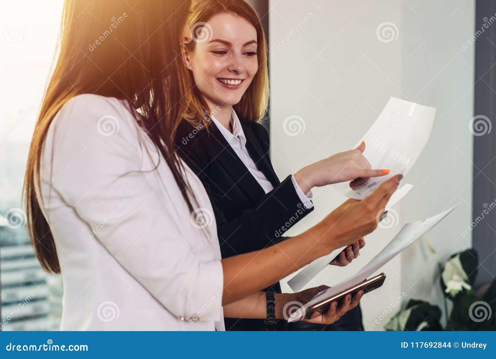 Frau und ihr Assistent, welche die Dokumente besprechen Unternehmensplan und Strategie am Arbeitsplatz verwahrt