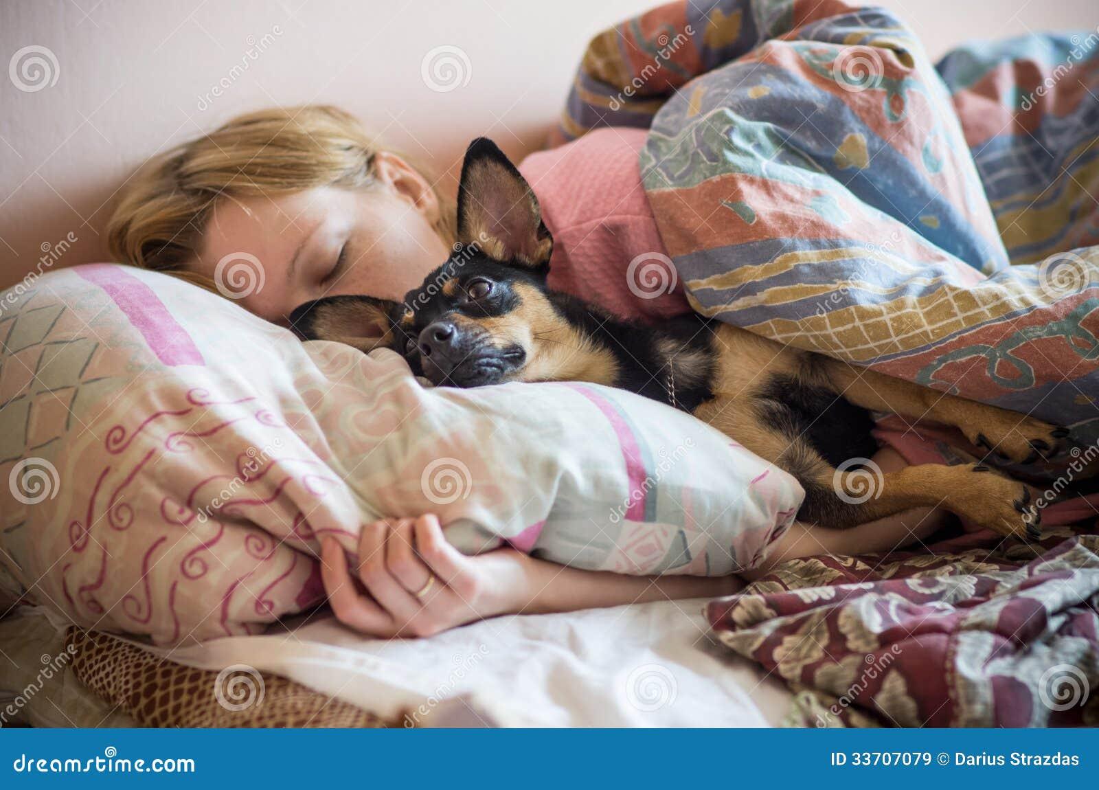Frau und ihr Hund, die im Bett schlafen