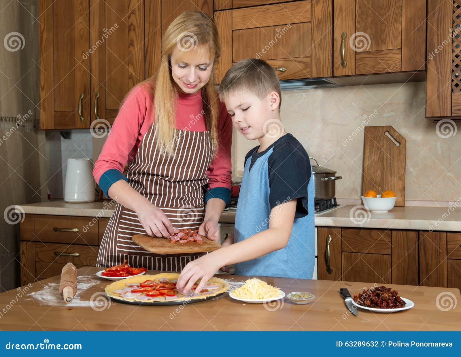 Frau und ihr Sohn, die zu Hause Pizza machen Jugendlichjunge, der mit seiner Mutter kocht