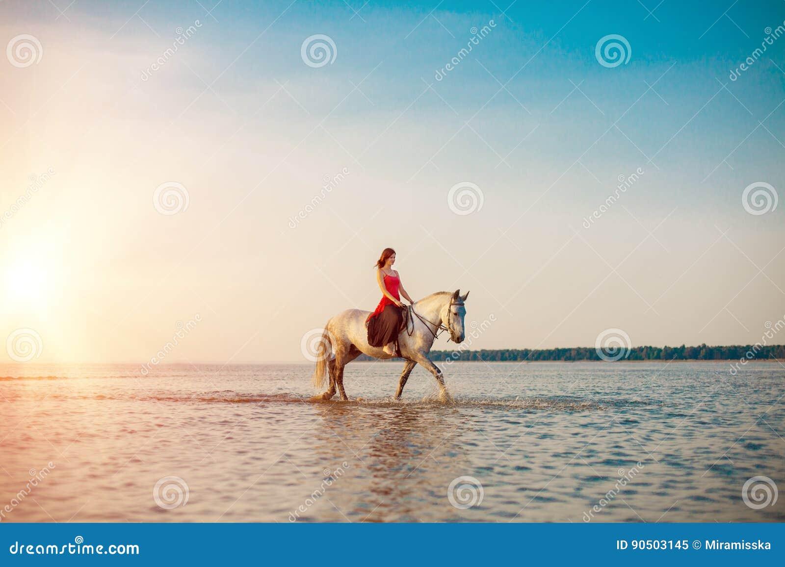 Frau und Pferd auf dem Hintergrund des Himmels und des Wassers Mädchen vorbildliches O