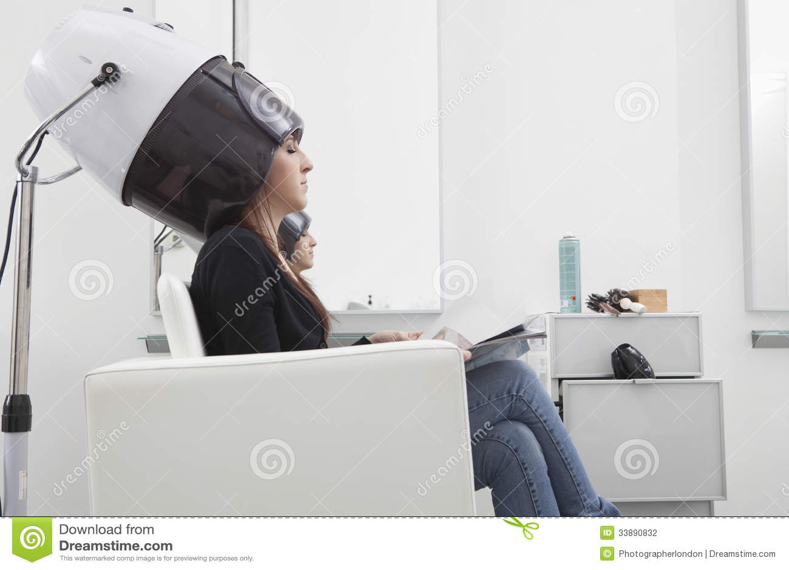 Frau unter mit kapuze trockner maschine im friseursalon stockfoto