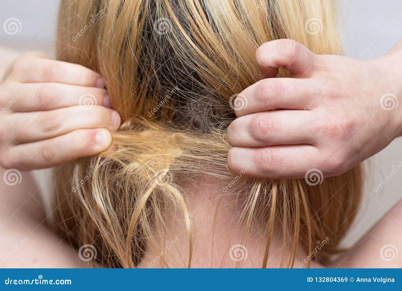 Frau versucht, einen Haarbüschel zu entwirren