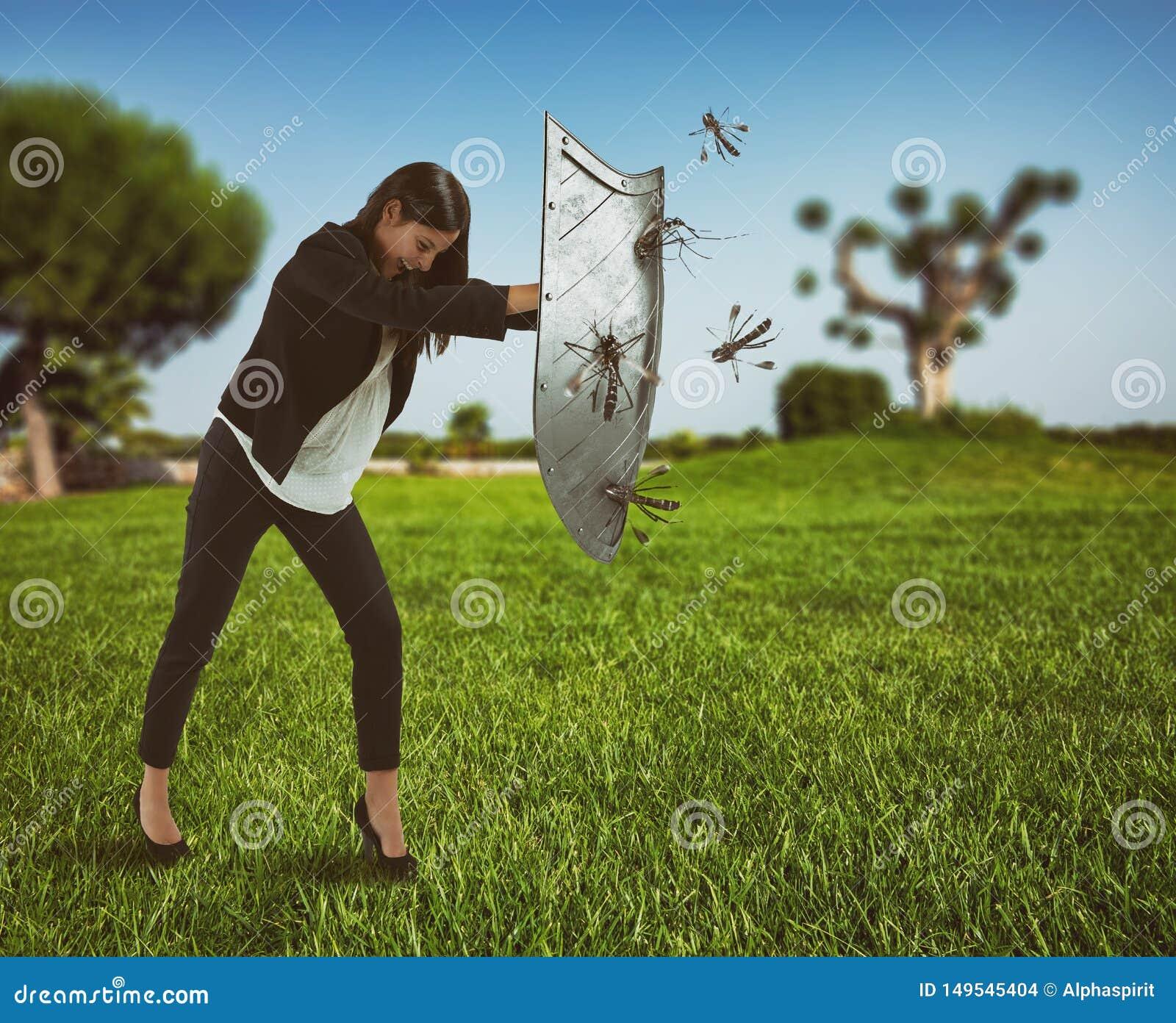 Frau verteidigt sich vom Angriff von Moskitos mit einem Schild