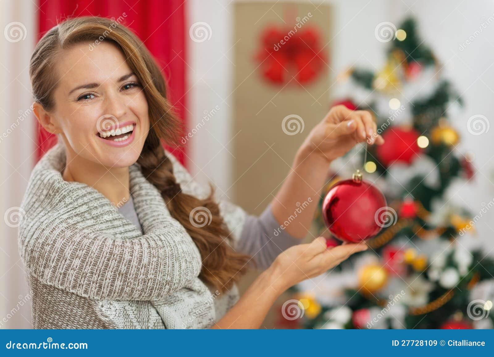 Frau vor Weihnachtsbaum-Holdingkugel