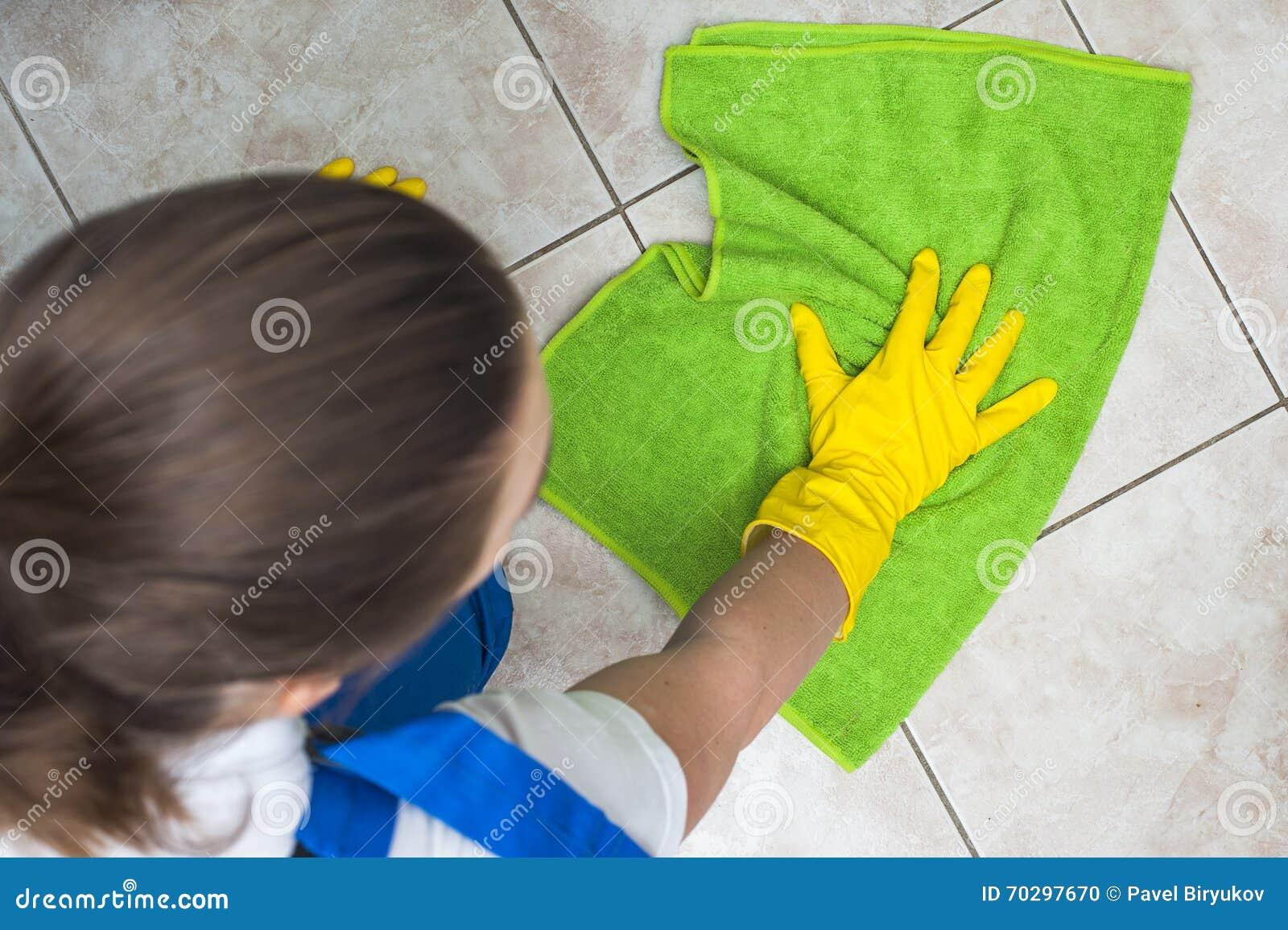 Frau in waschenden Böden der Arbeitskleidung mit grünem Lappen