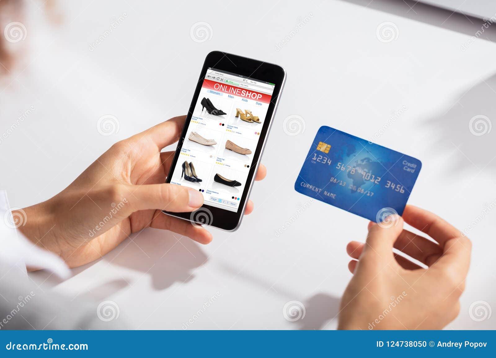 Frau, welche in der Hand die Kreditkarte tut das on-line-Einkaufen hält