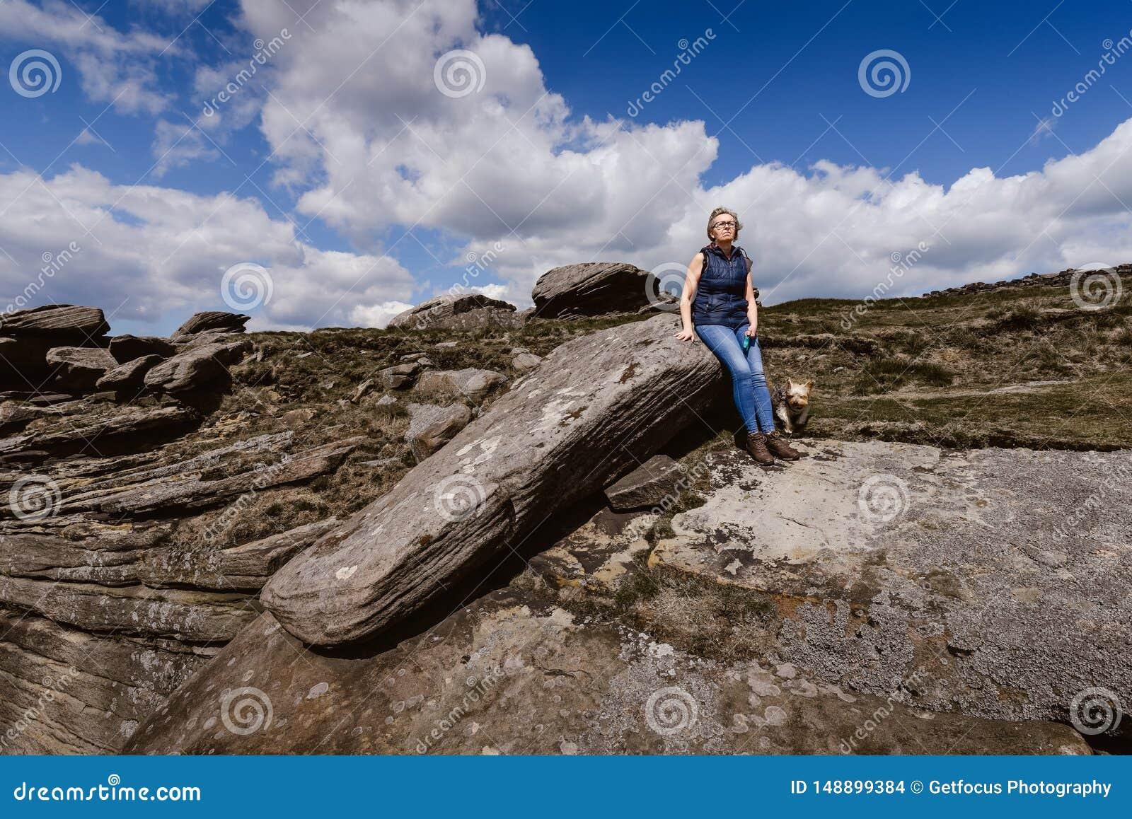 Frau, welche die Ansicht an Derbyshire-Felsen aufpasst