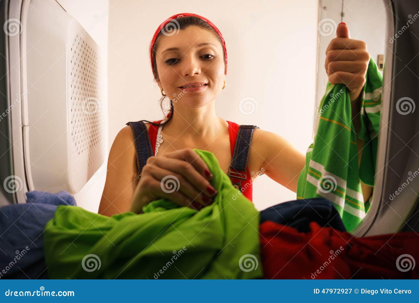 Frau welche die haushaltung zu hause nimmt trockene kleidung vom