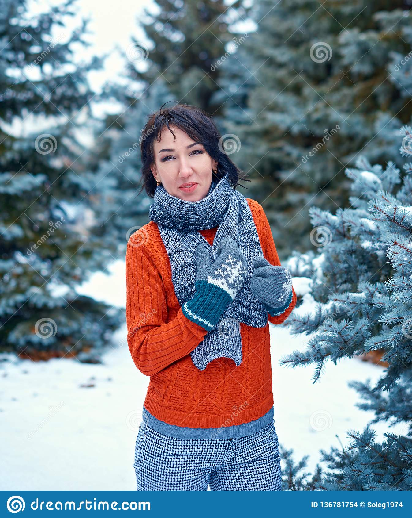 Frau wirft im Winterwald, schöne Landschaft mit schneebedeckten Tannenbäumen auf Angekleidet in der roten Strickjacke
