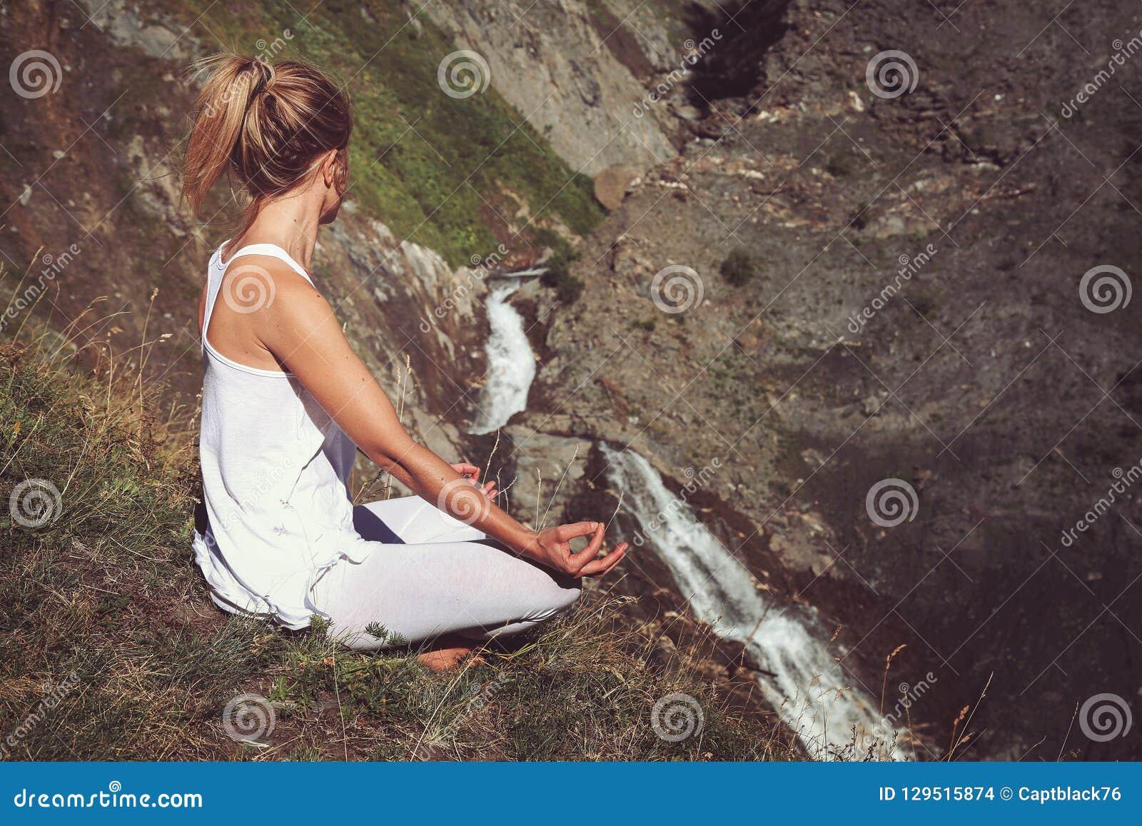 Frau in Yoga positiion Blicken auf Wasserfall