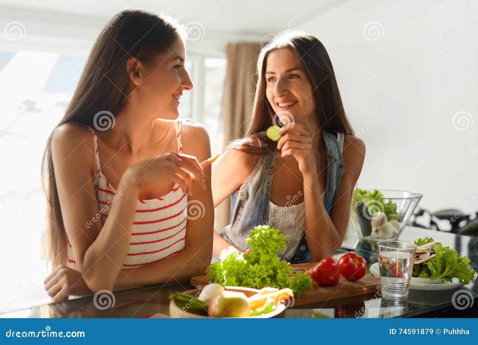 Frauen der gesunden Ernährung, die Salat in der Küche kochen Eignungs-Diät-Lebensmittel