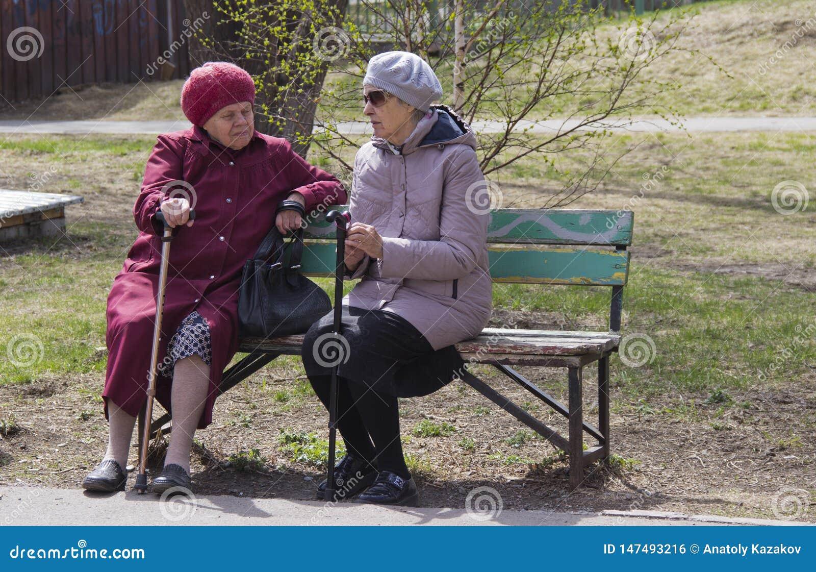 Frauen des Pensionsalters sitzen auf einer Bank und besprechen die Nachrichten