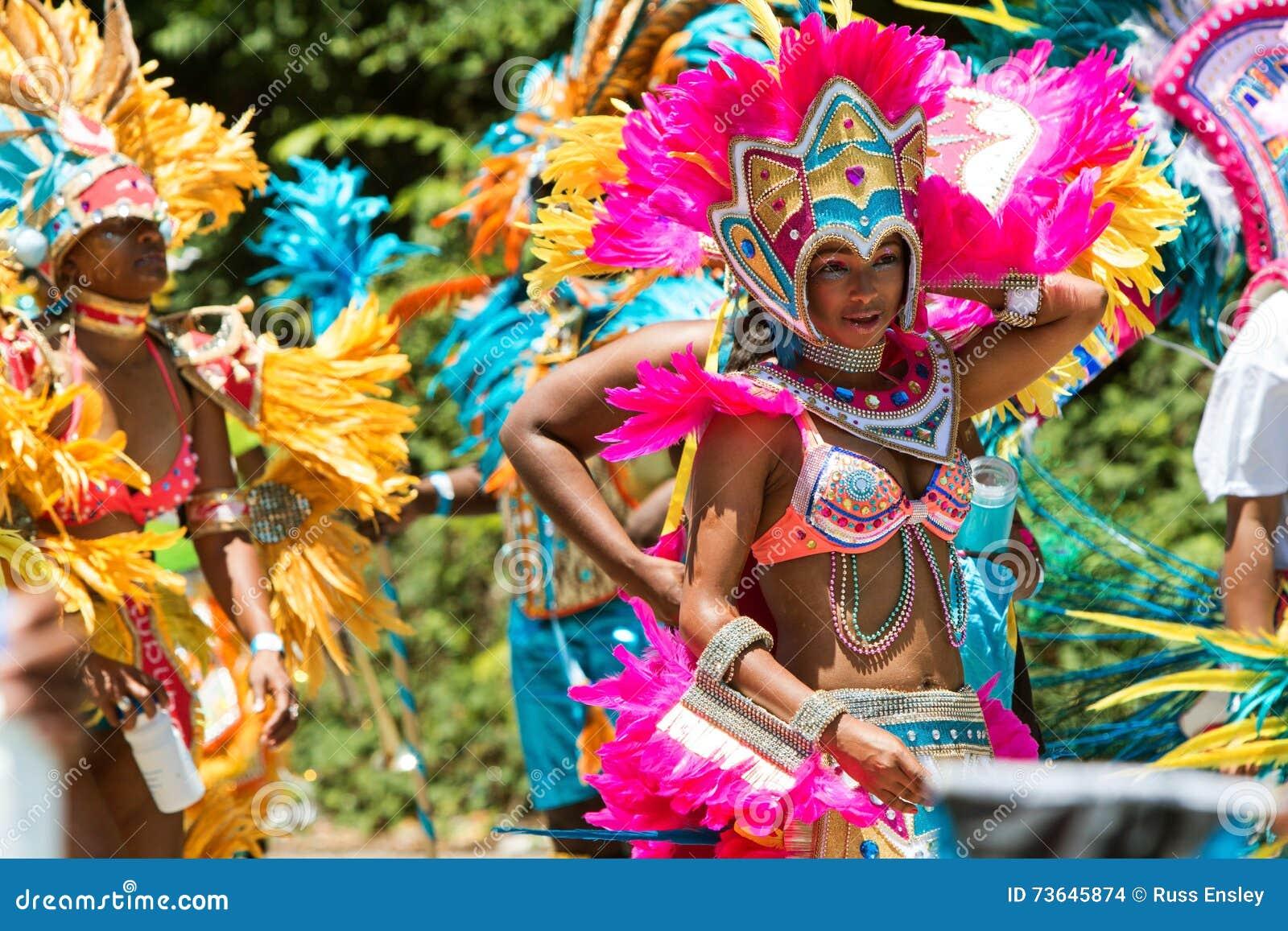 Frauen, die Kostüme und mit Federn versehenen Kopfschmuck-Weg in der karibischen Parade tragen