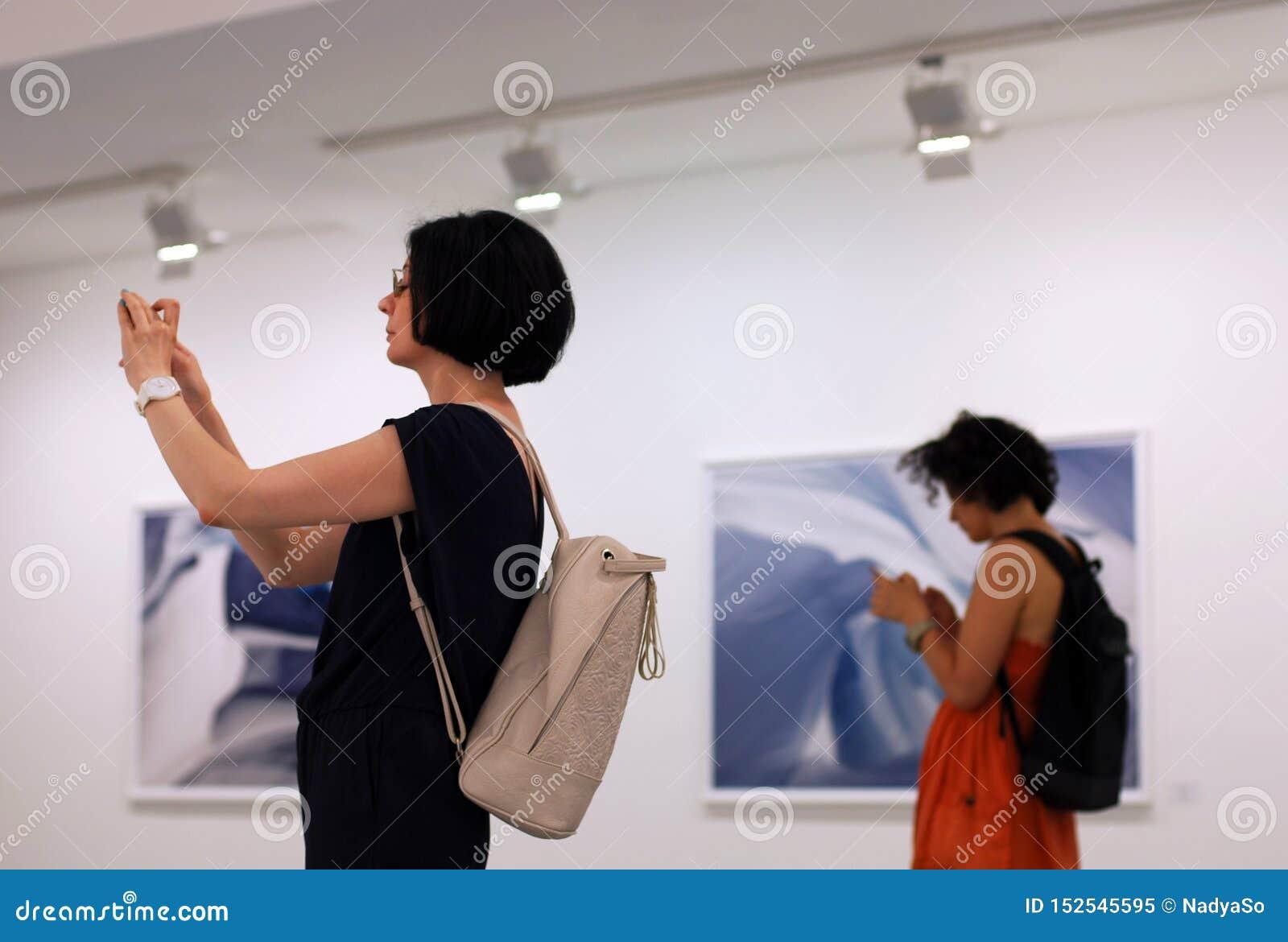 Frauen an Foto exhition unter Verwendung der Smartphones, tragbare Geräte und Sucht des Sozialen Netzes