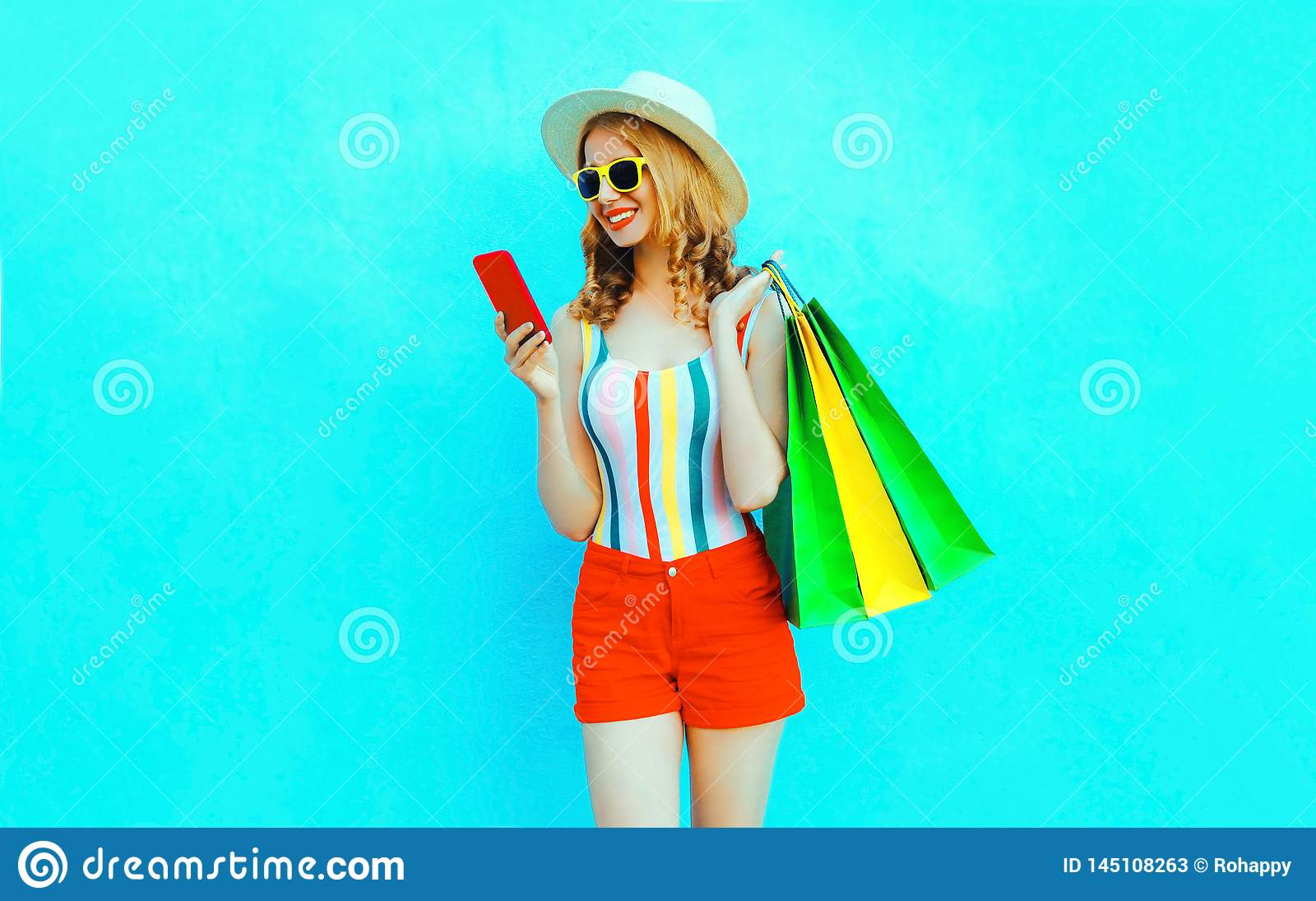 Frauen-Holdingtelefon des Porträts glückliches lächelndes mit Einkaufstaschen im bunten T-Shirt, Sommerstrohhut, Sonnenbrille,