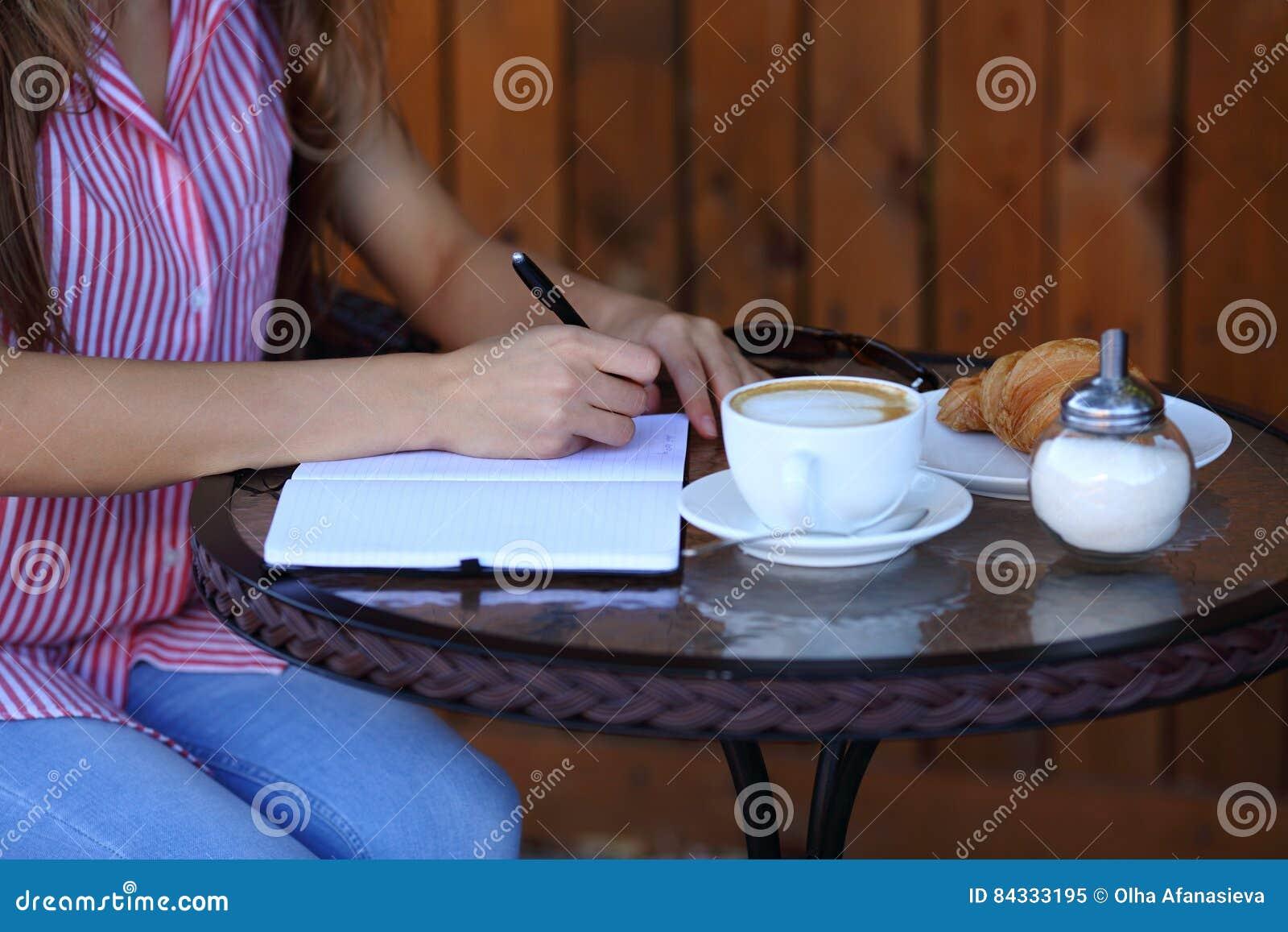 Frauen ` s übergibt Schreiben im Tagebuch mit Kaffee