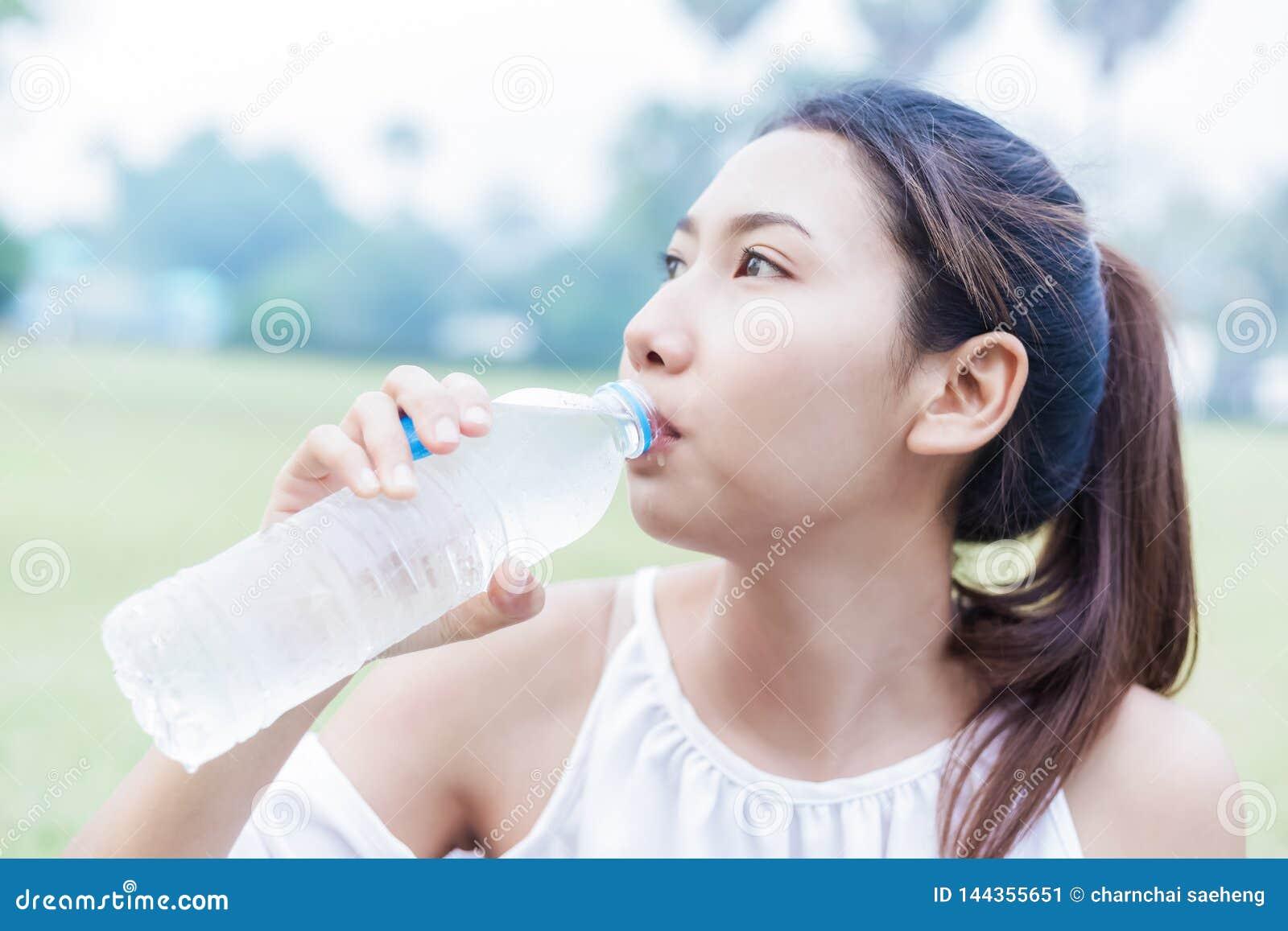 Frauen trinken Wasser von der Flasche im Park