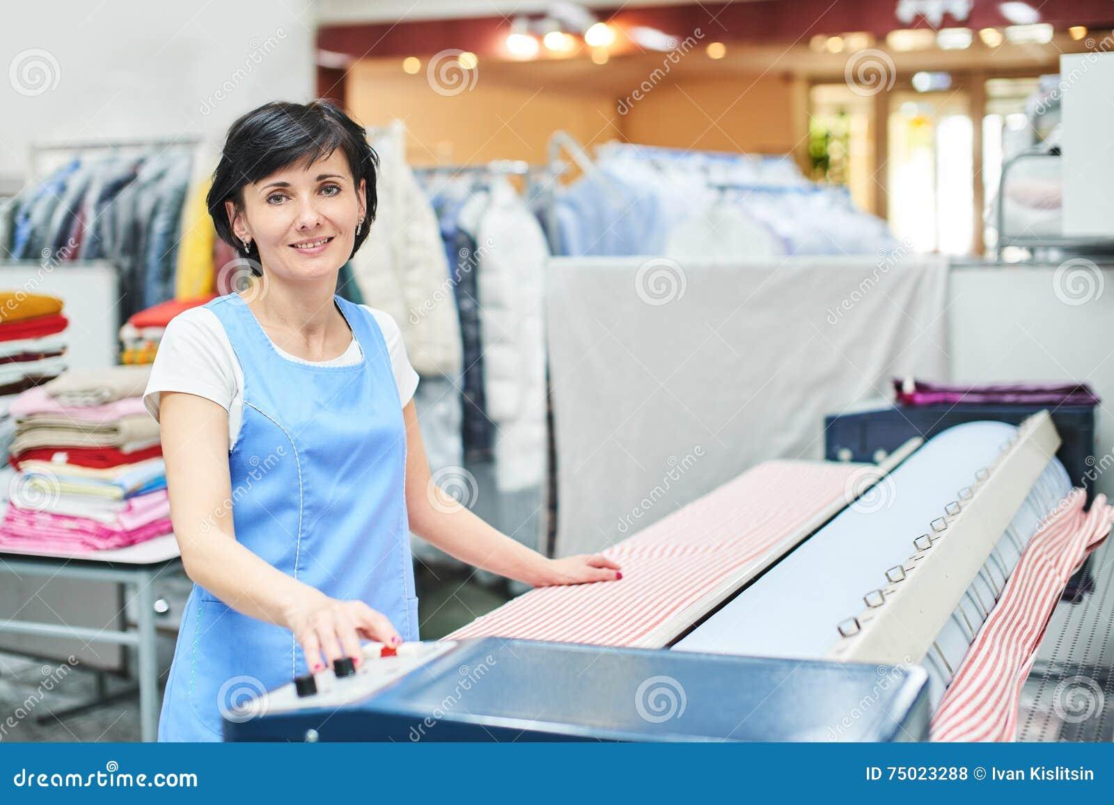 Frauen-Wäschereiarbeitskraft tappt das Leinen auf dem Automaten