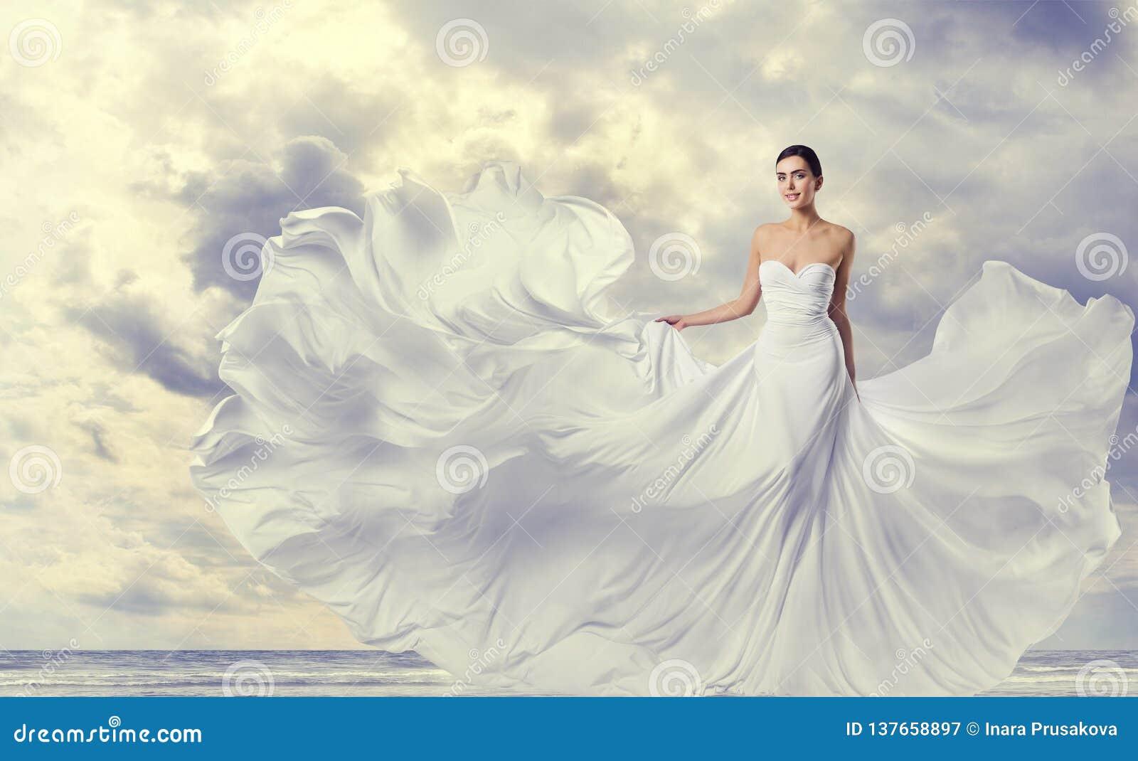 Frauen-weißes Kleid, Mode-Modell in lange Seiden-flatterndem Kleid, wellenartig bewegender fliegender Stoff auf Wind