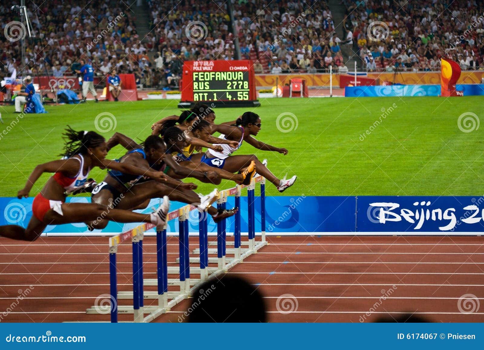 Frauen, welche die 100M Hürden laufen
