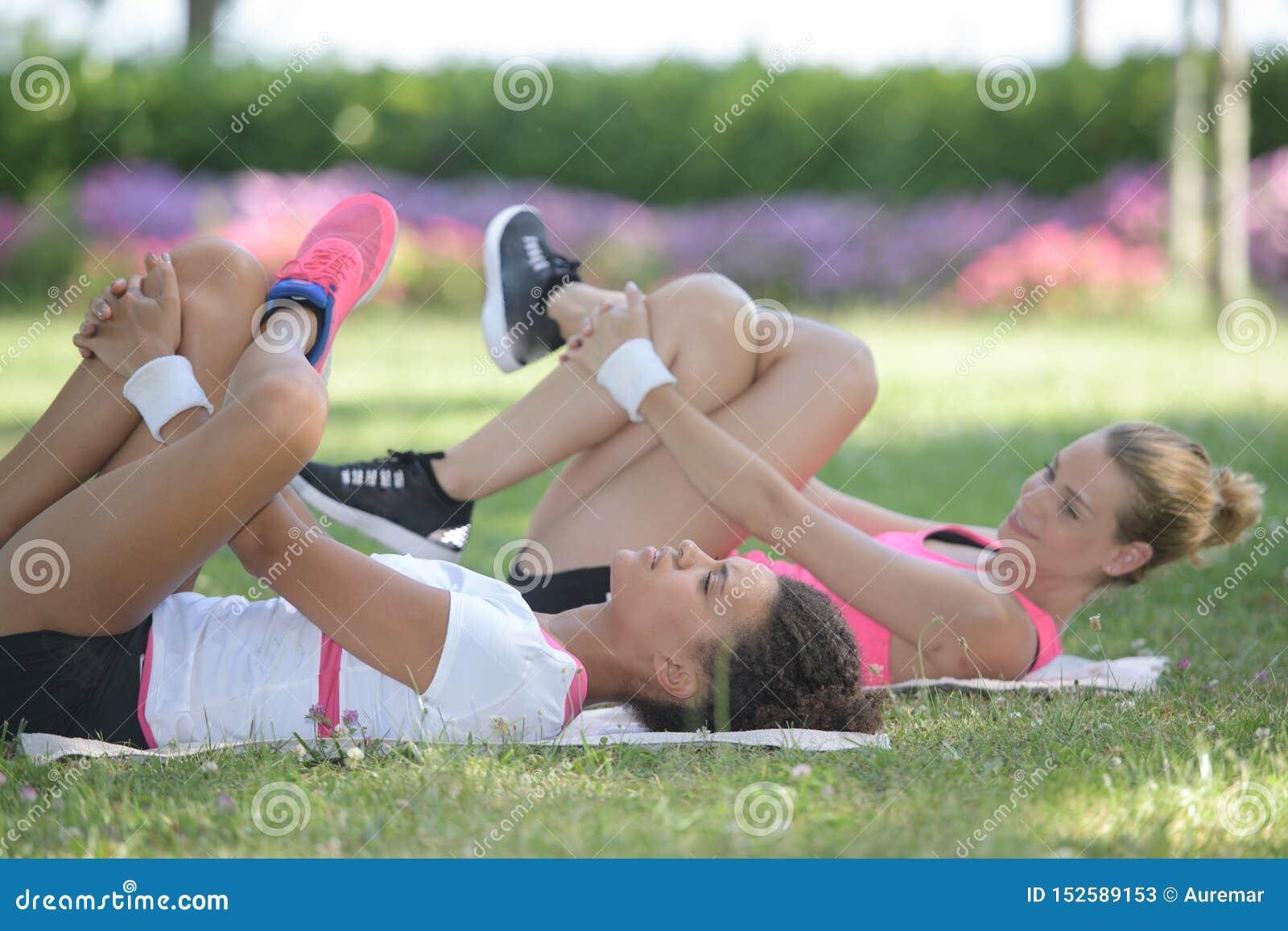 Frauen, welche die Beinübungen gelegt auf Gras tun