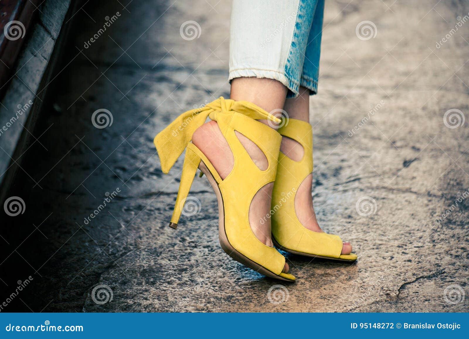 Frauenbeine in den ledernen gelben Sandalen des hohen Absatzes im Freien in der Stadt