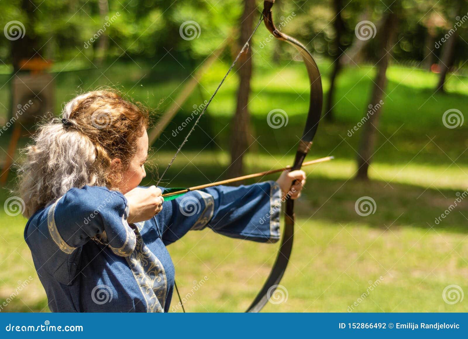Frauenbogenschütze mit Bogentriebpfeil im Wald auf Ritterfestival in einer traditionellen Klage