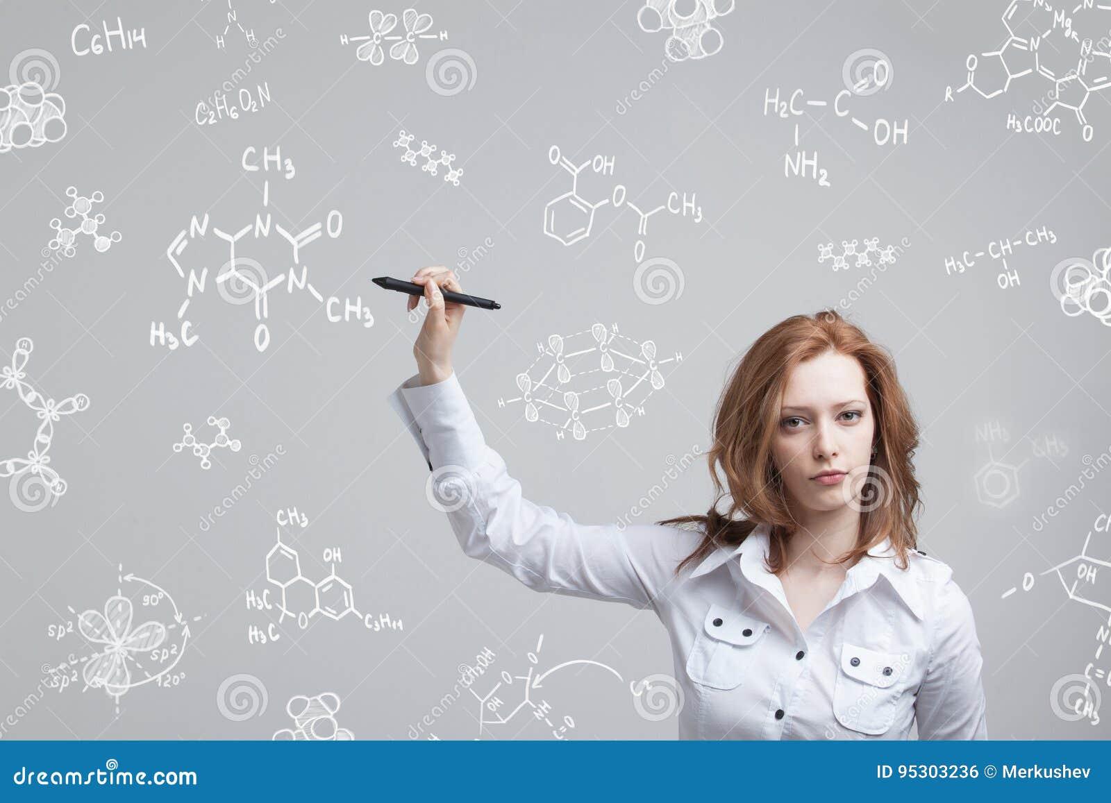 Frauenchemiker, der mit chemischen Formeln auf grauem Hintergrund arbeitet