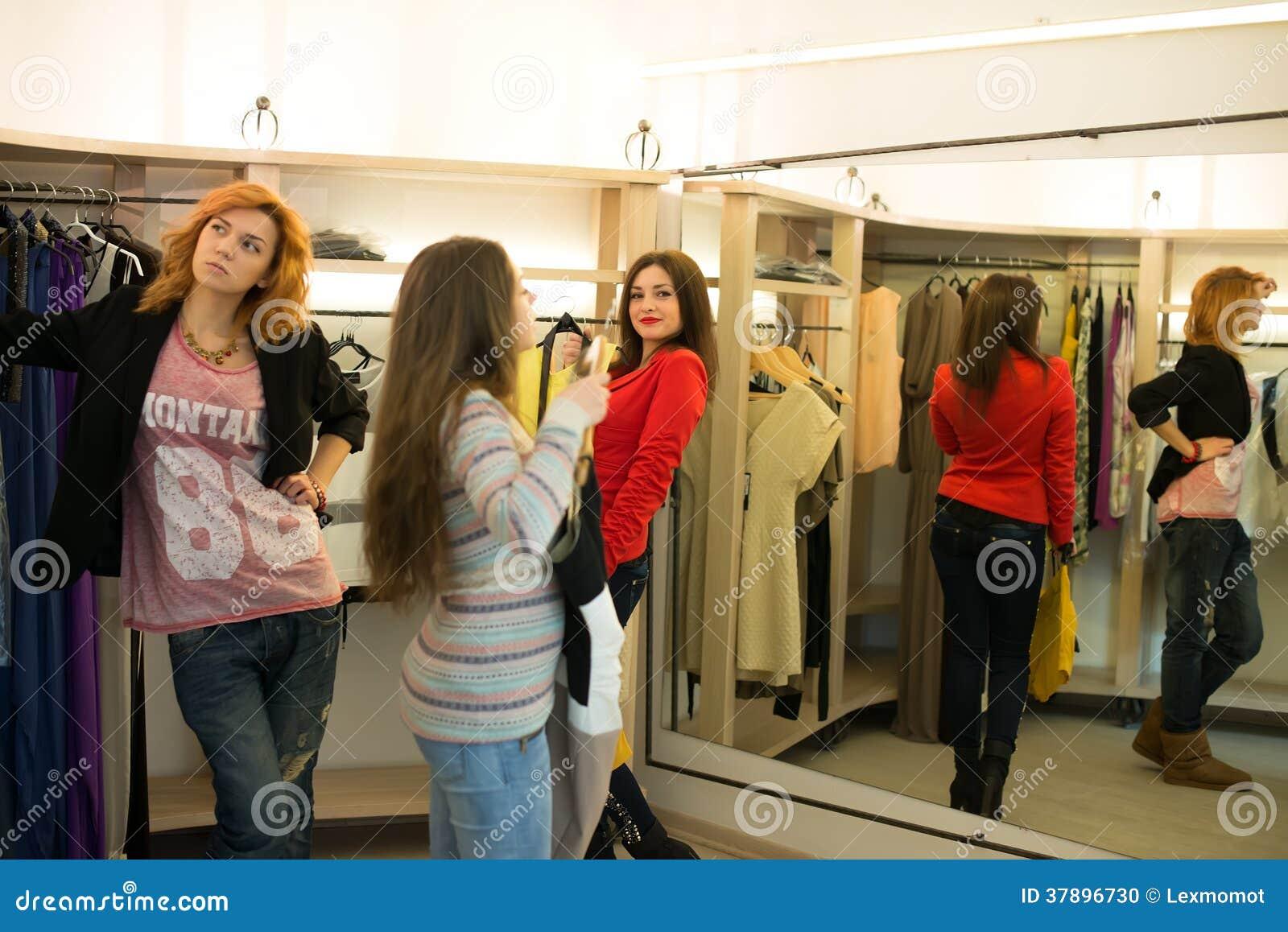 Fraueneinkaufen, welches die Kleider schauen im Spiegel unsicher wählt