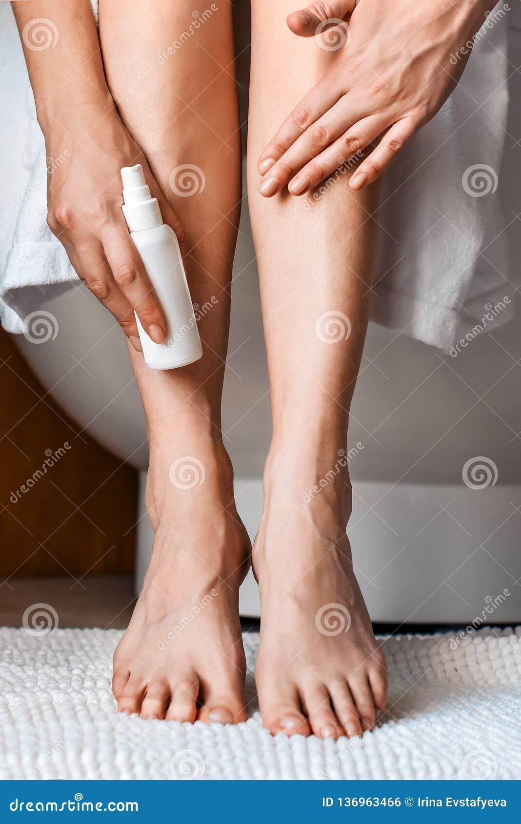 Frauenfuß im Wasser Junge Frau im Badezimmer, ihre Beine streichend Anti-Cellulitebehandlung für schöne gut-gepflegte Beine
