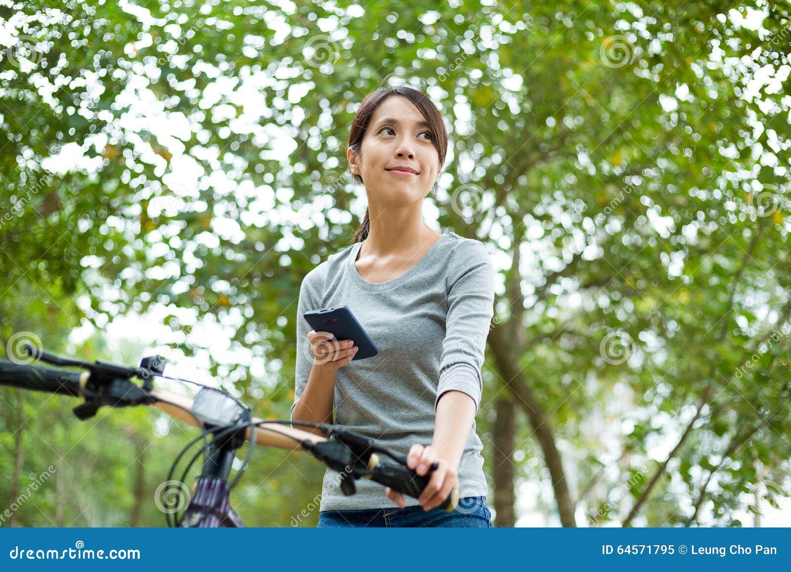 Frauengebrauch des intelligenten Telefons und des Reitens eines Fahrrades