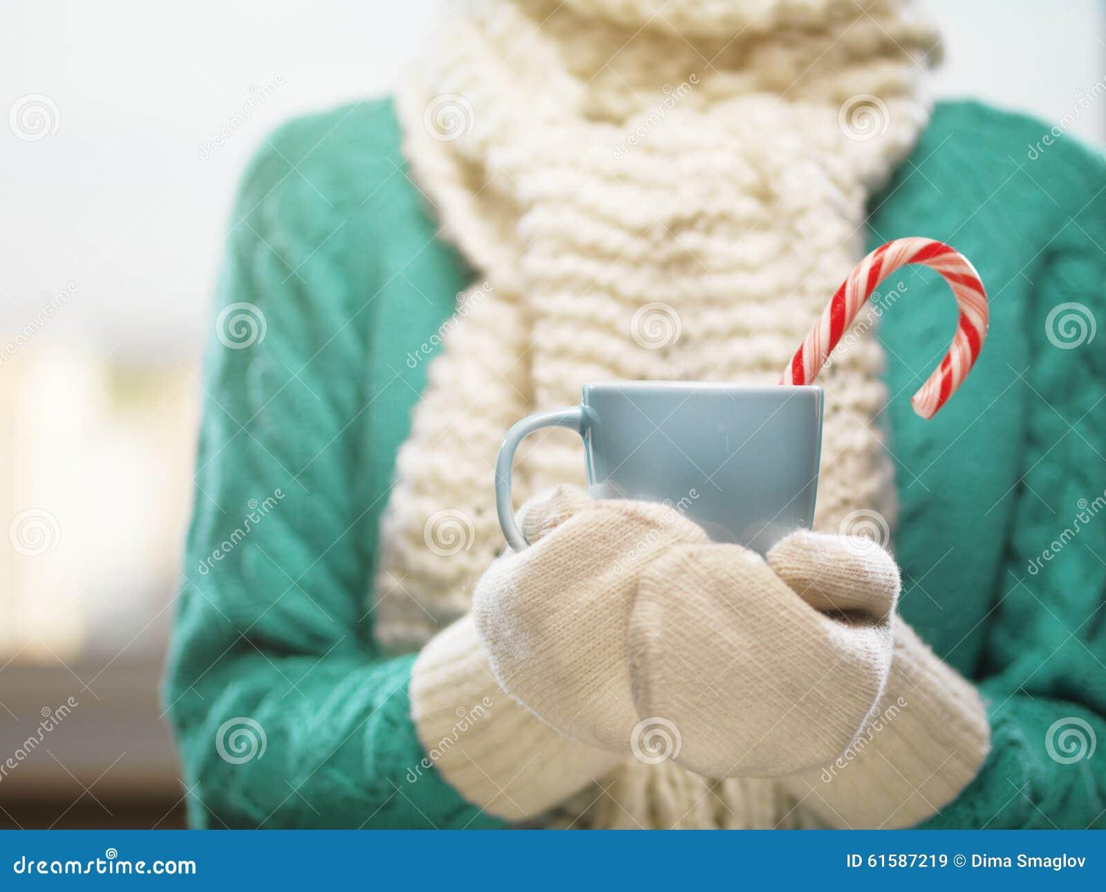 Frauenhände in den weißen woolen Handschuhen, die eine gemütliche Schale mit heißem Kakao, Tee oder Kaffee halten Winter- und Wei