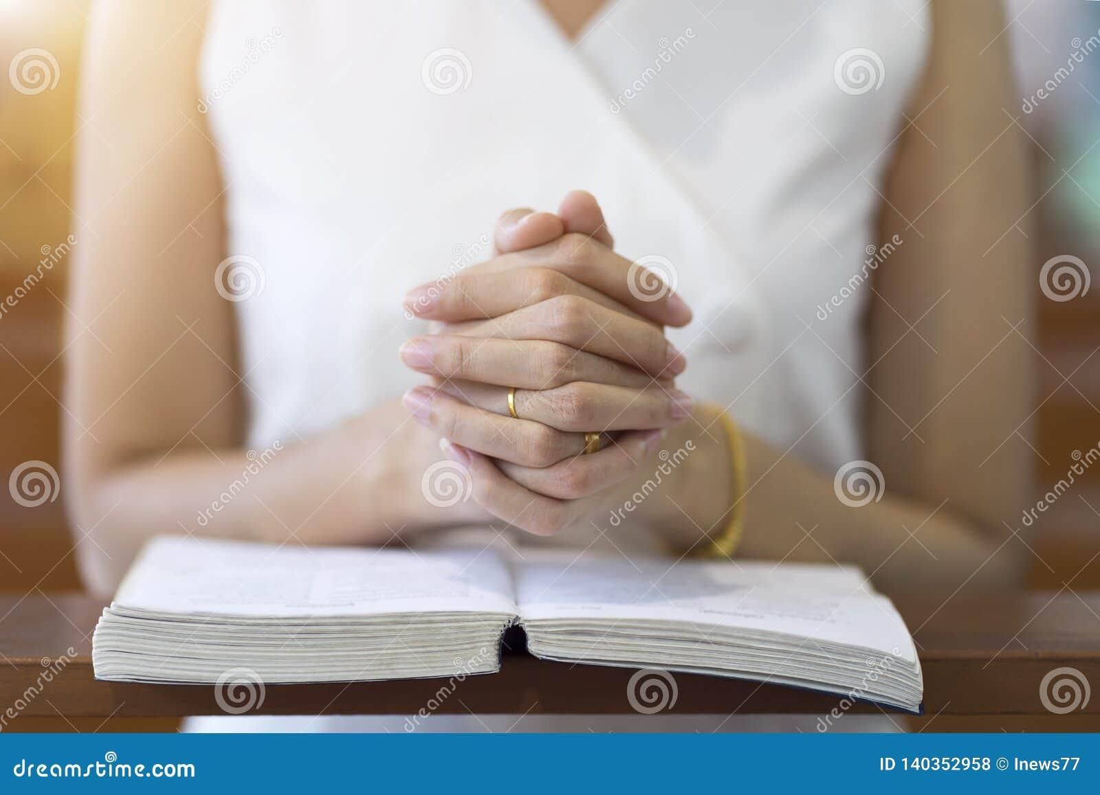 Frauenhände, die auf einer heiligen Bibel in der Kirche für Glaubenkonzept, Geistigkeit und christliche Religion beten