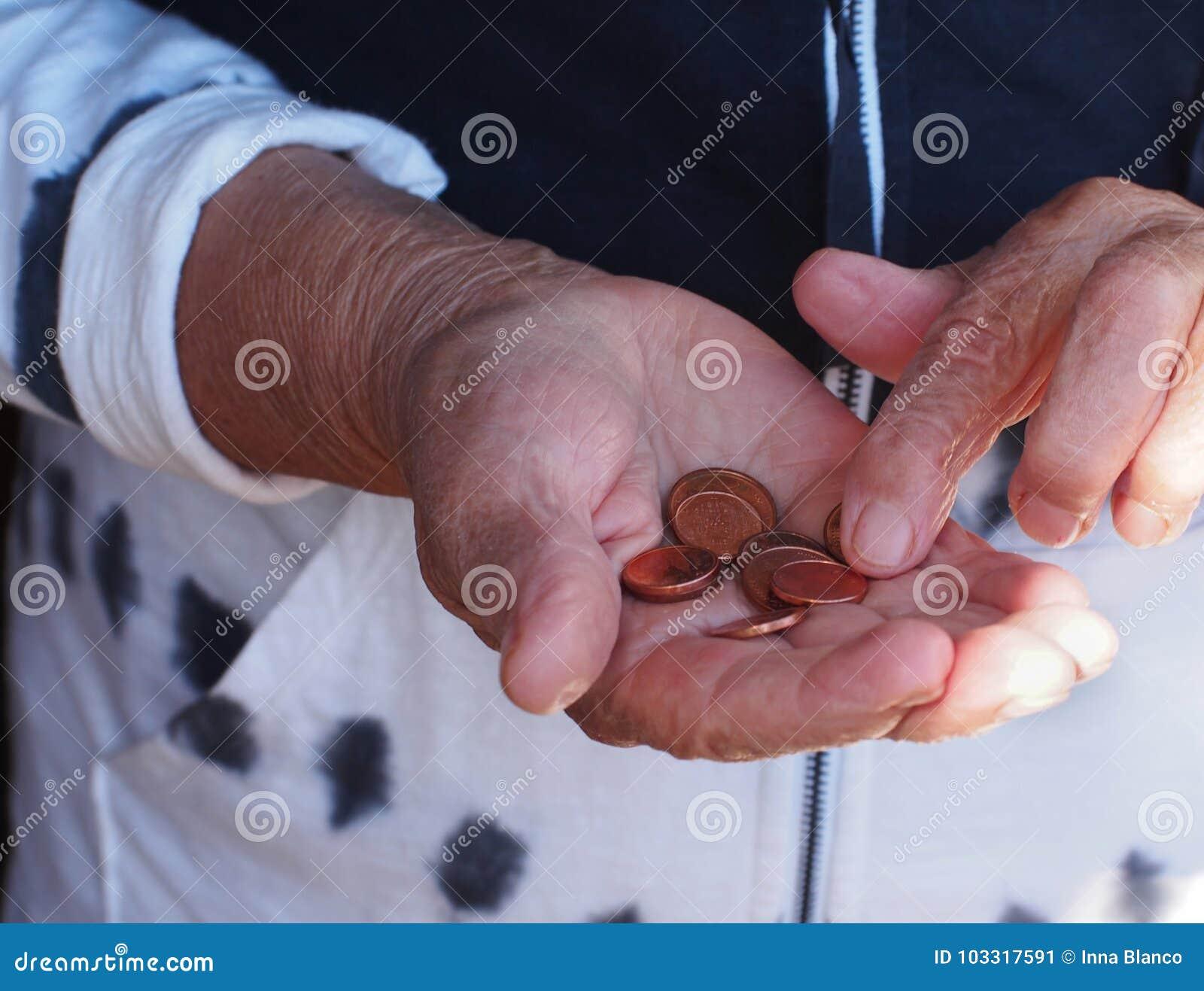 Frauenhände, die einige Euromünzen halten Pension, Armut, Sozialprobleme und Altersschwächethema