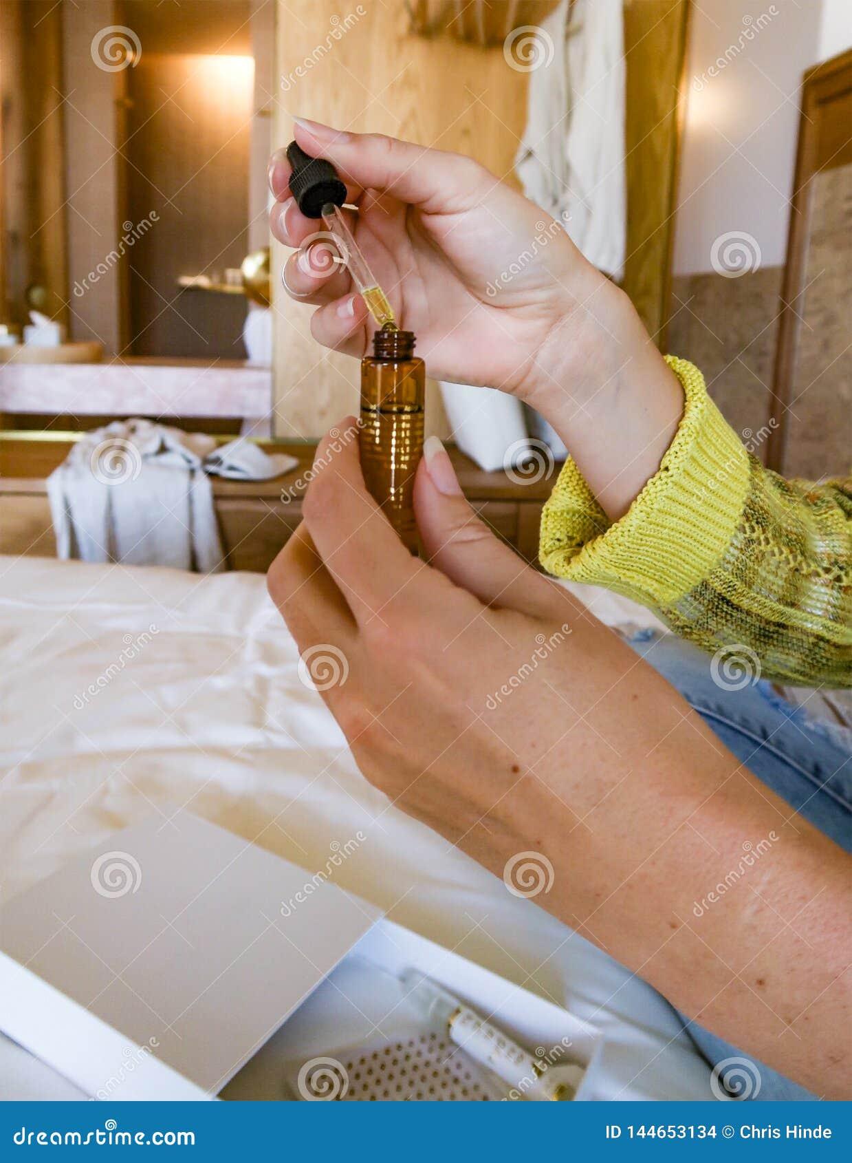 Frauenhände mit einem Augentropfenzähler